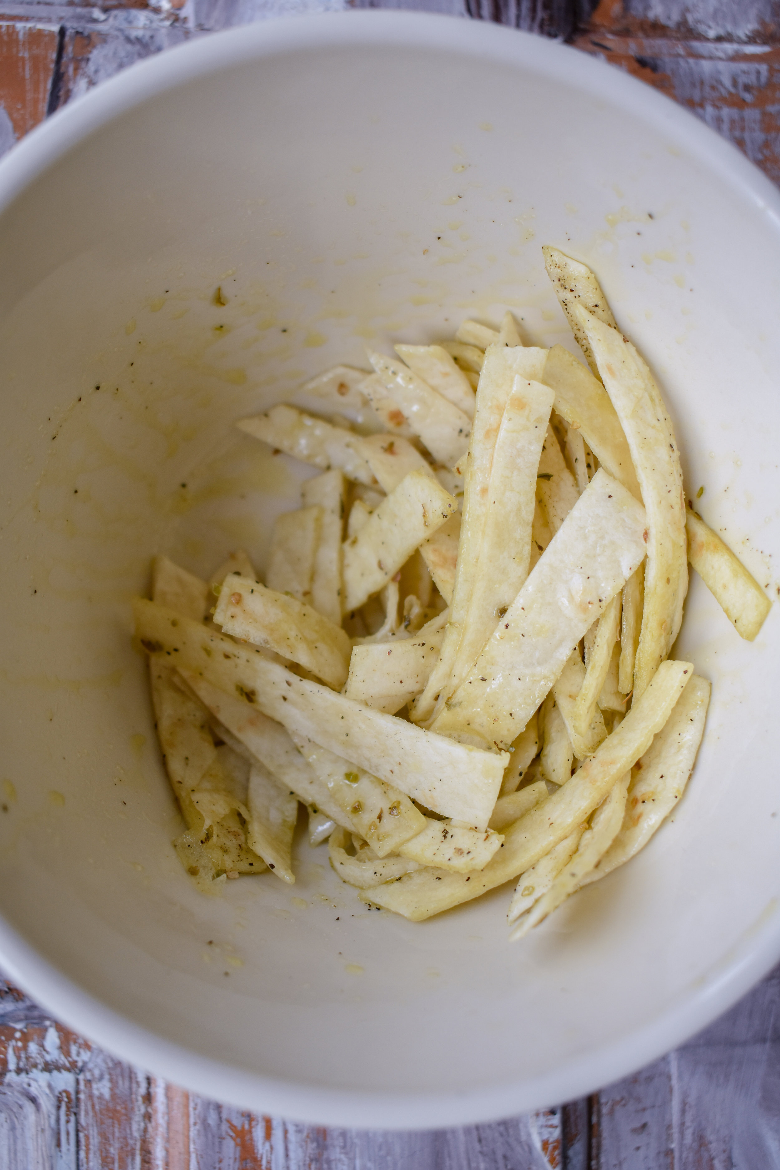 7. The last bit of prep is the tortilla strips. Stack them on top of each other and cut in 1/2, stack again so you have 8 equal pieces, then cut small strips from the cut edge to the rounded edge about 1/4 inch in width. Add the strips to a bowl, mix with the avocado oil, salt, and pepper.