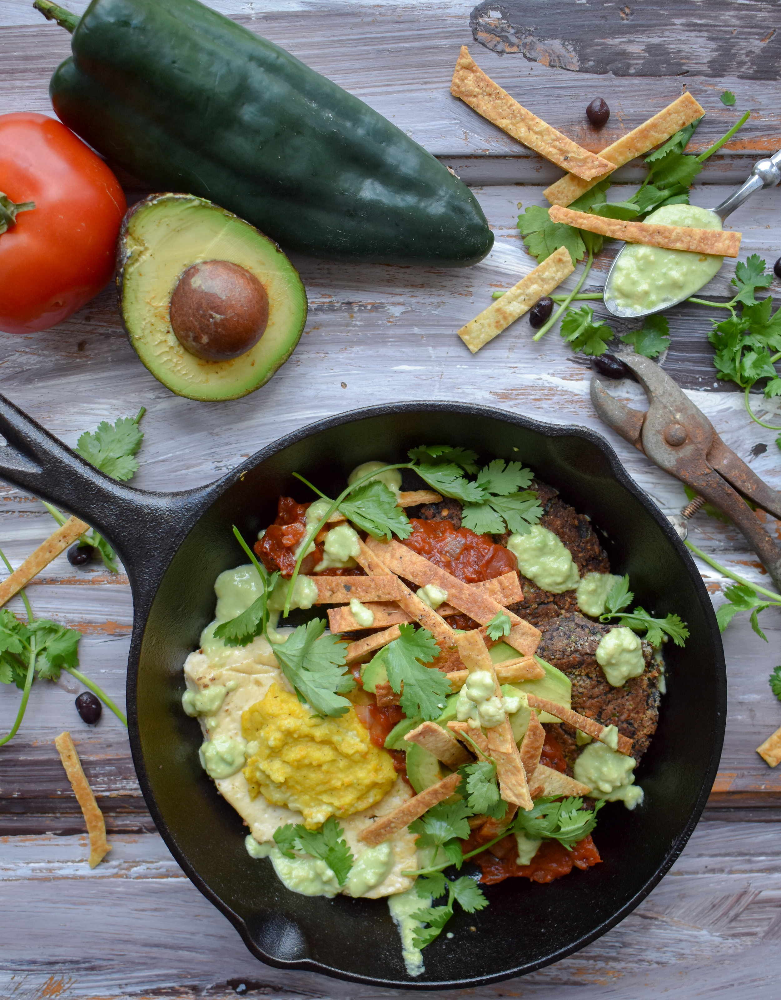 13. To serve, plate with two black bean cakes, one plant egg (add the yolk), pour on 1/4 of the ranchero sauce, add some fresh avocado slices, cilantro, tortilla strips, and drizzle on the avocado crema. YUM YUM YUM YUM YUM !!!!