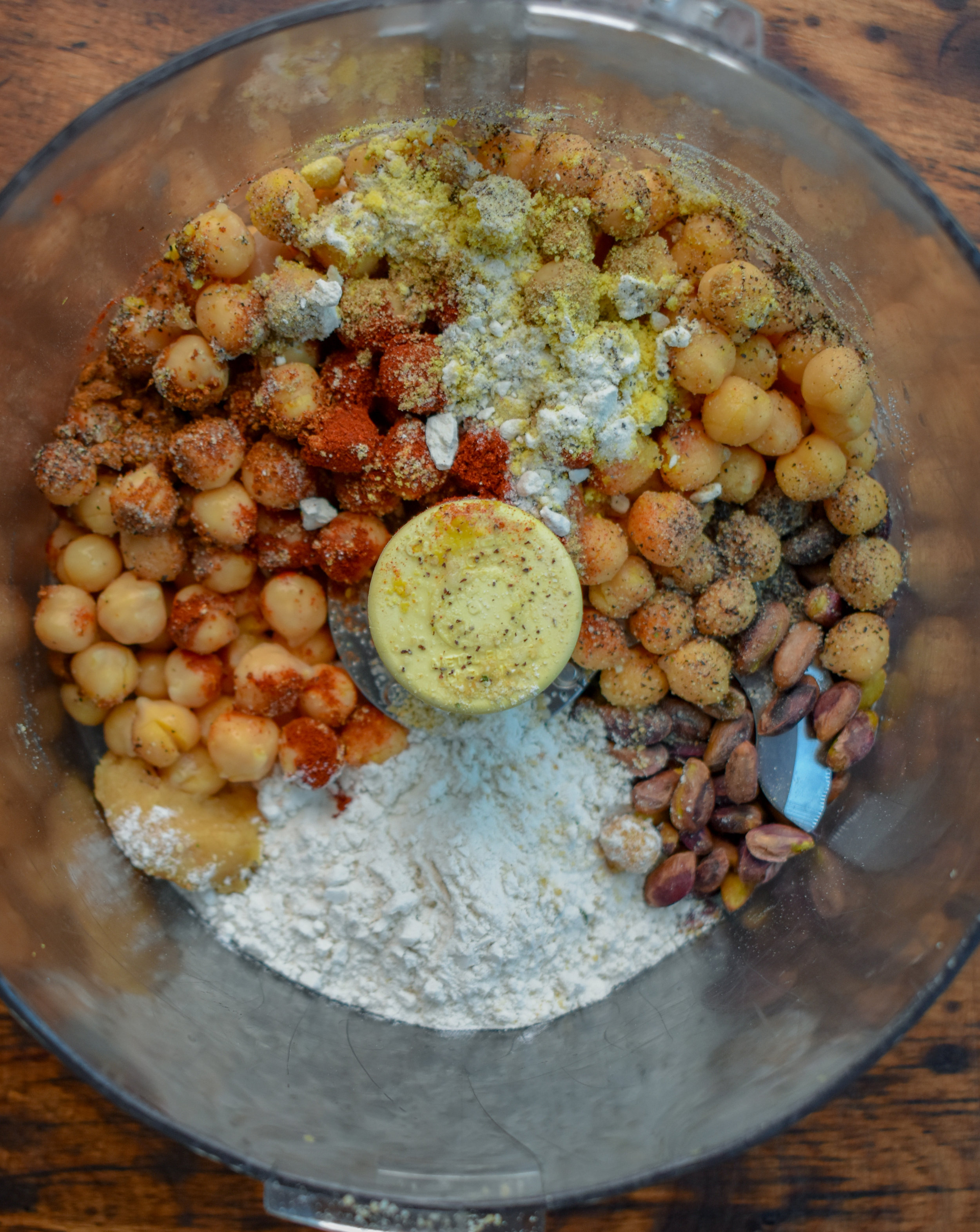 3.  To a food processor/high-speed blender add pistachios, chickpeas, chili powder, paprika, oregano, coriander, pepper, and salt. Pulse 10-15 times until the chickpeas are broken down into very small pieces.