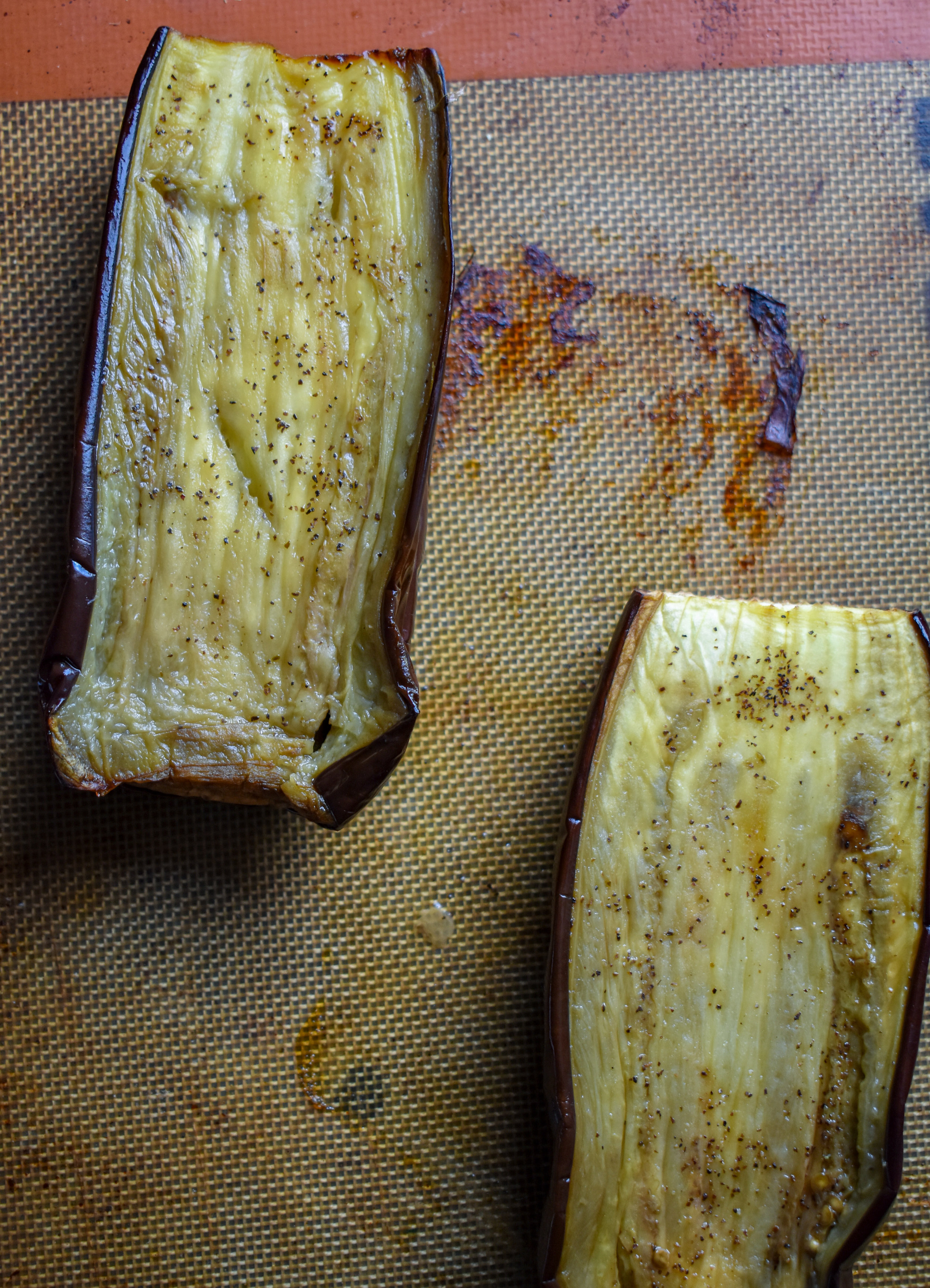 1. Cut your eggplant in 1/2 long ways. Brush on or rub on 1 tbl of olive oil and sprinkle with a pinch of salt + pepper. Place the halves face down on a parchment-lined or silpat-lined baking sheet. Place into the oven at 350F and cook for 40-45 minutes.