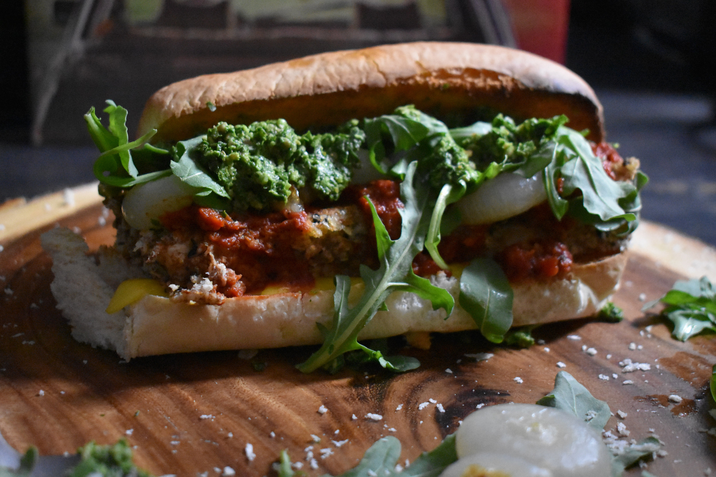 8. To finish the sandwich, add bread sliced open and a few 1/2 slices of vegan cheese to oven and broil at 525F for 5-6 minutes. Then layer on cutlets, tomato sauce, onions, pesto, and arugula.