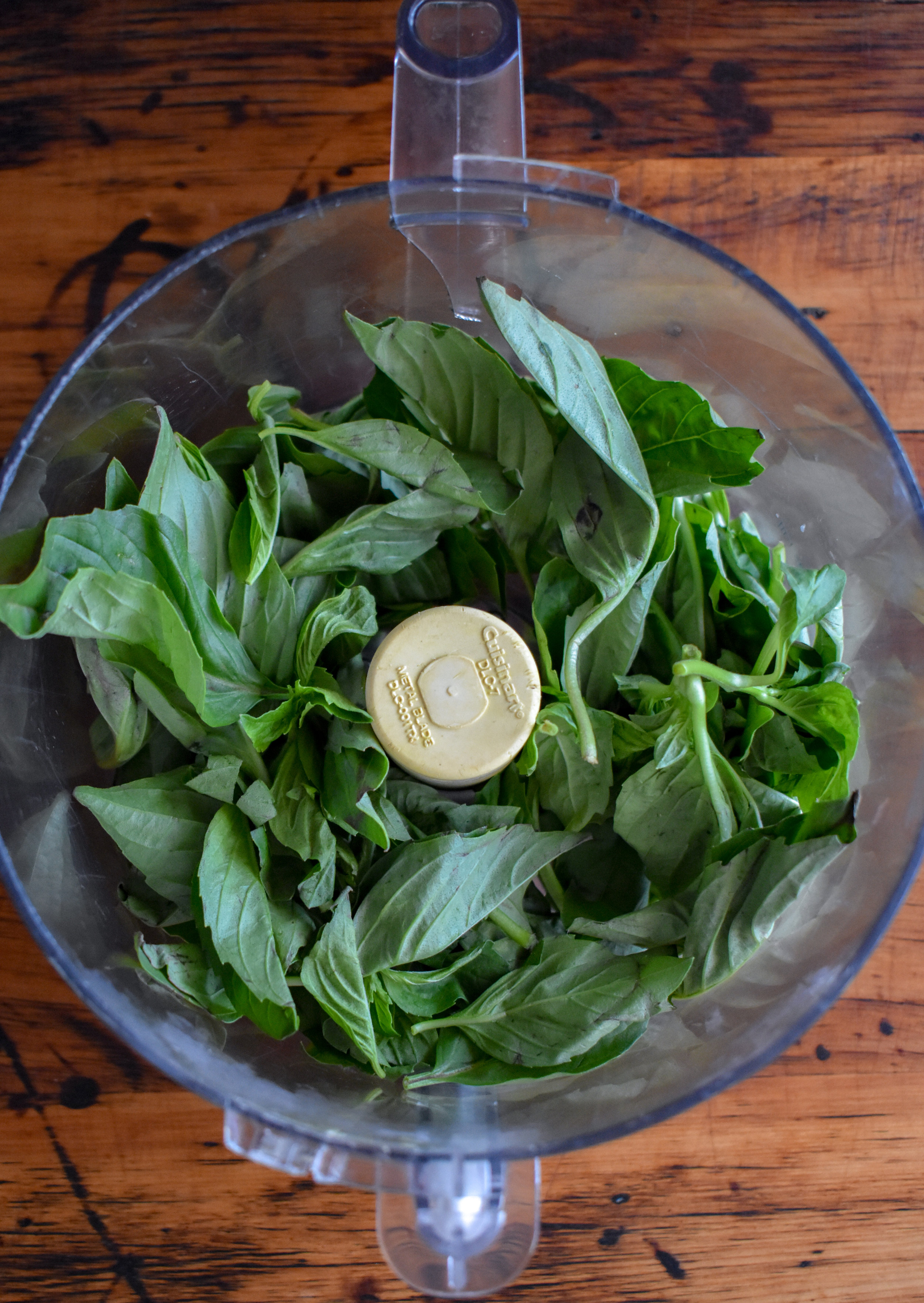 1. Add basil to a food processor. Pulse 5-6 times to start to break down the basil.