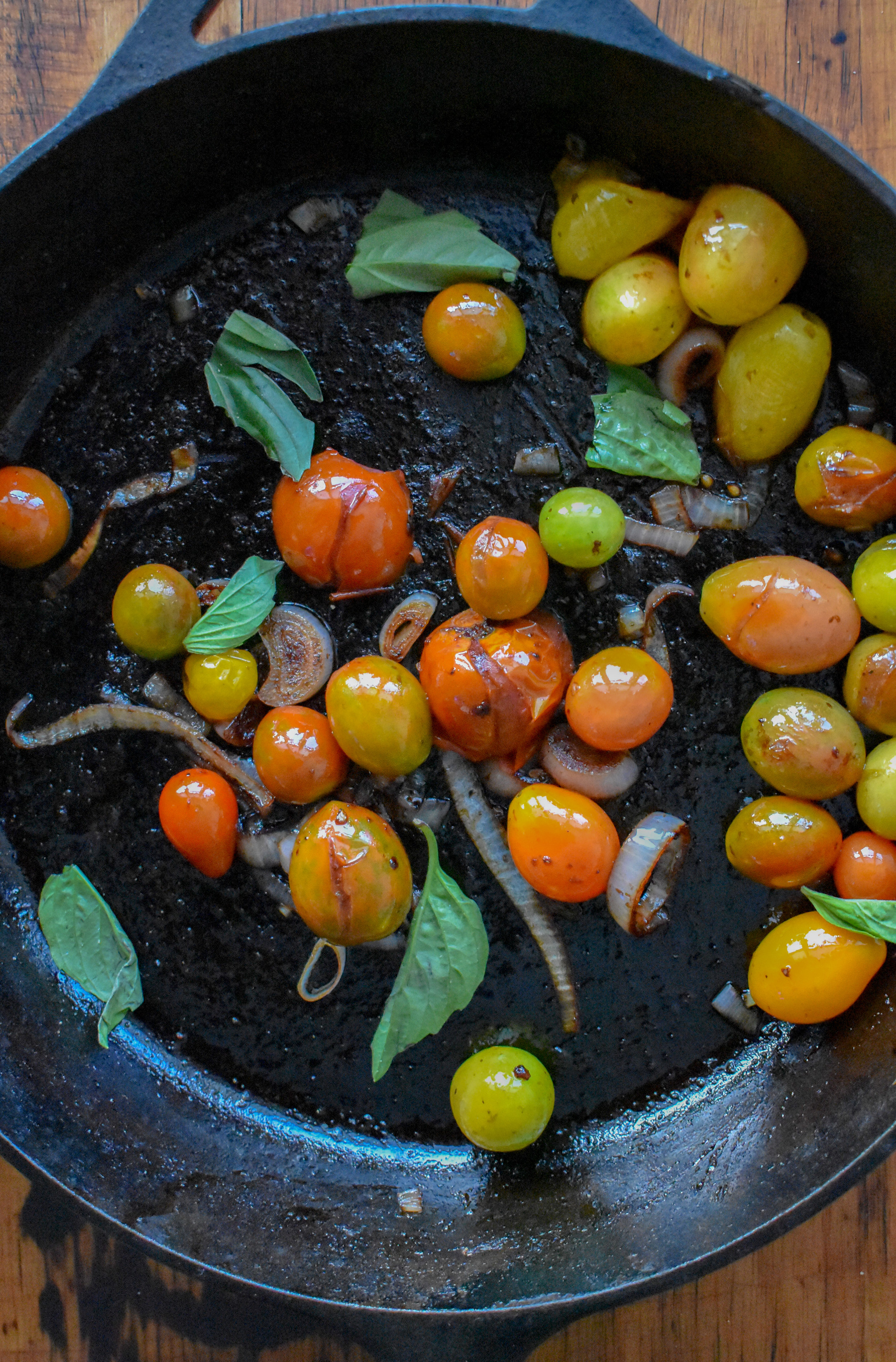 2. While the potatoes are cooking, heat olive oil for tomatoes in a castiron or large frying pan. Heat for 90 seconds and then add shallots + garlic. Cook for 2-3 minutes before adding cherry tomatoes. Continue to cook over medium heat for 2-3 minutes on each side until it starts to brown and tomatoes start to break open a bit. Add in some fresh basil (optional) after removing from heat. Set aside.