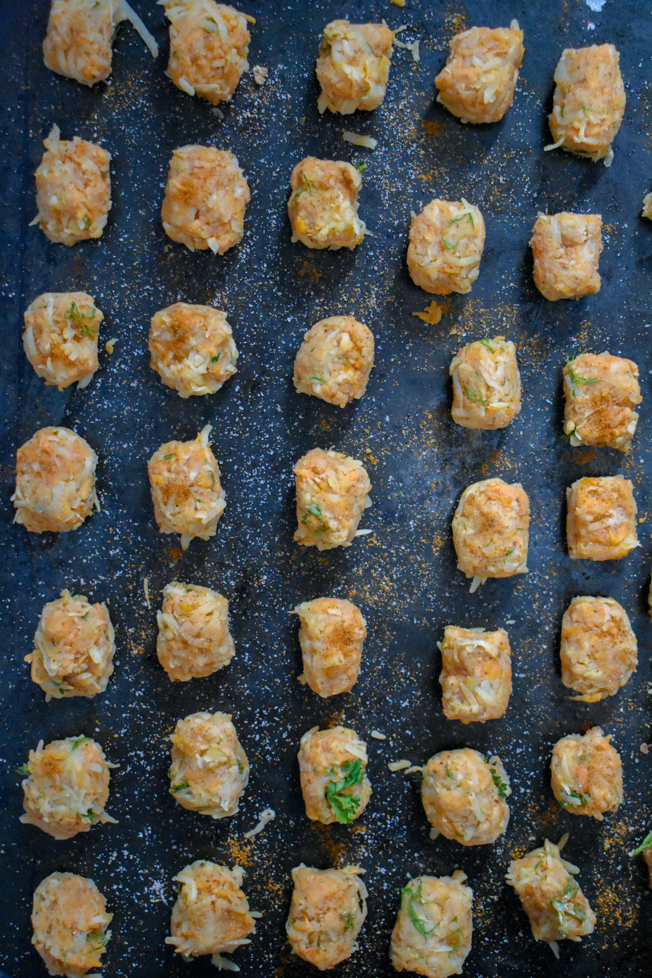 5. Next, use a spoon to scoop out about 1-2 tbl of the mixture and in your hand and place on a (important) oiled baking sheet. Please make sure to rub 1-2 tbl of oil on the baking sheet before adding tots. They'll stick if you don't. Place into oven at 400F for ~25minutes.