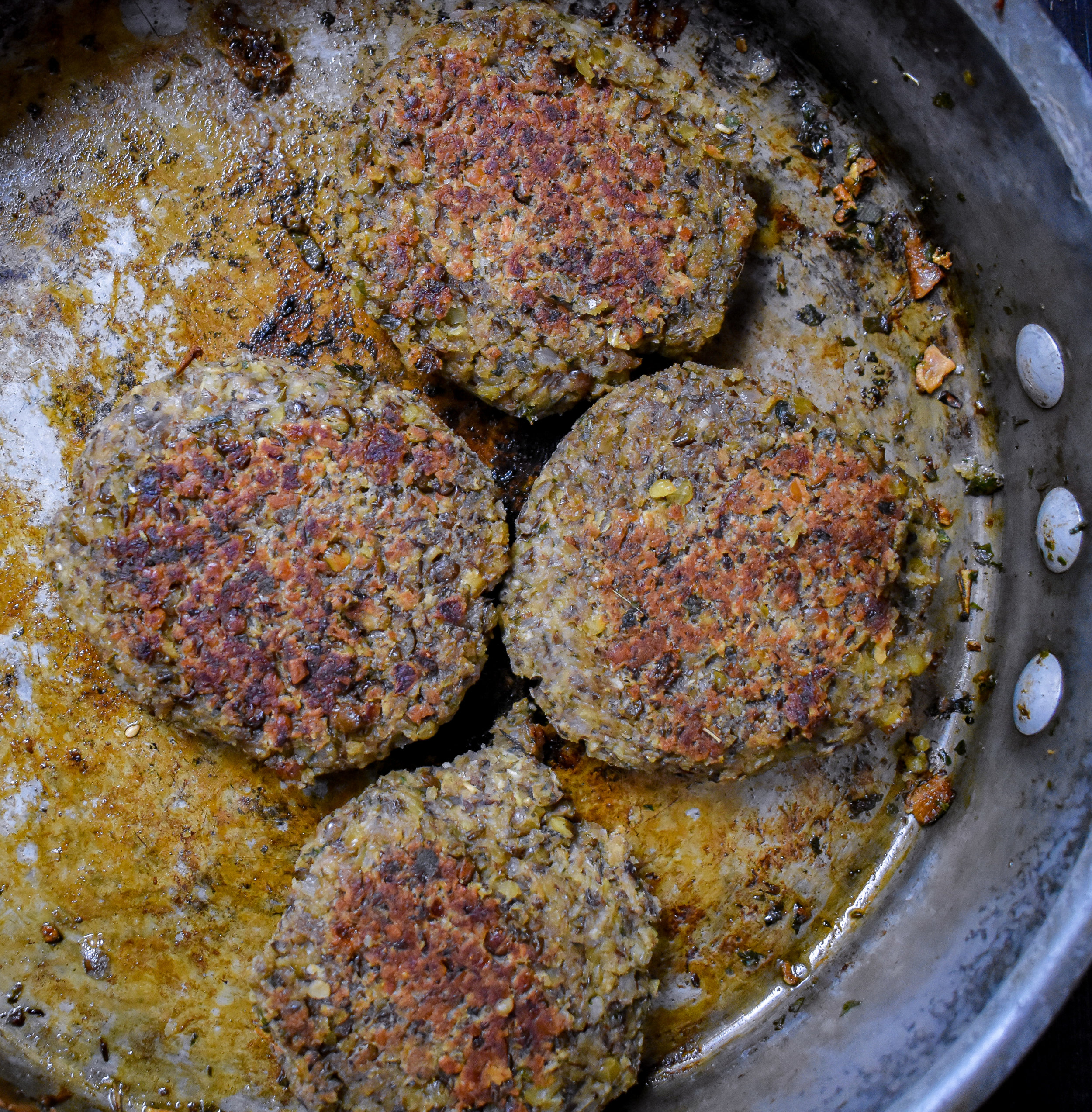 4. Next, form the mixture into 4 large sausage patties with your hands. If its feels very sticky, add some oat flour, cornstarch, or other flour. You should have a bit of residue on your hands but the patty should not be sticking to your hand. Add the patties back to the large frying pan with 1 tbl of olive oil. Cook over medium heat for ~4 minutes on each side until browned.