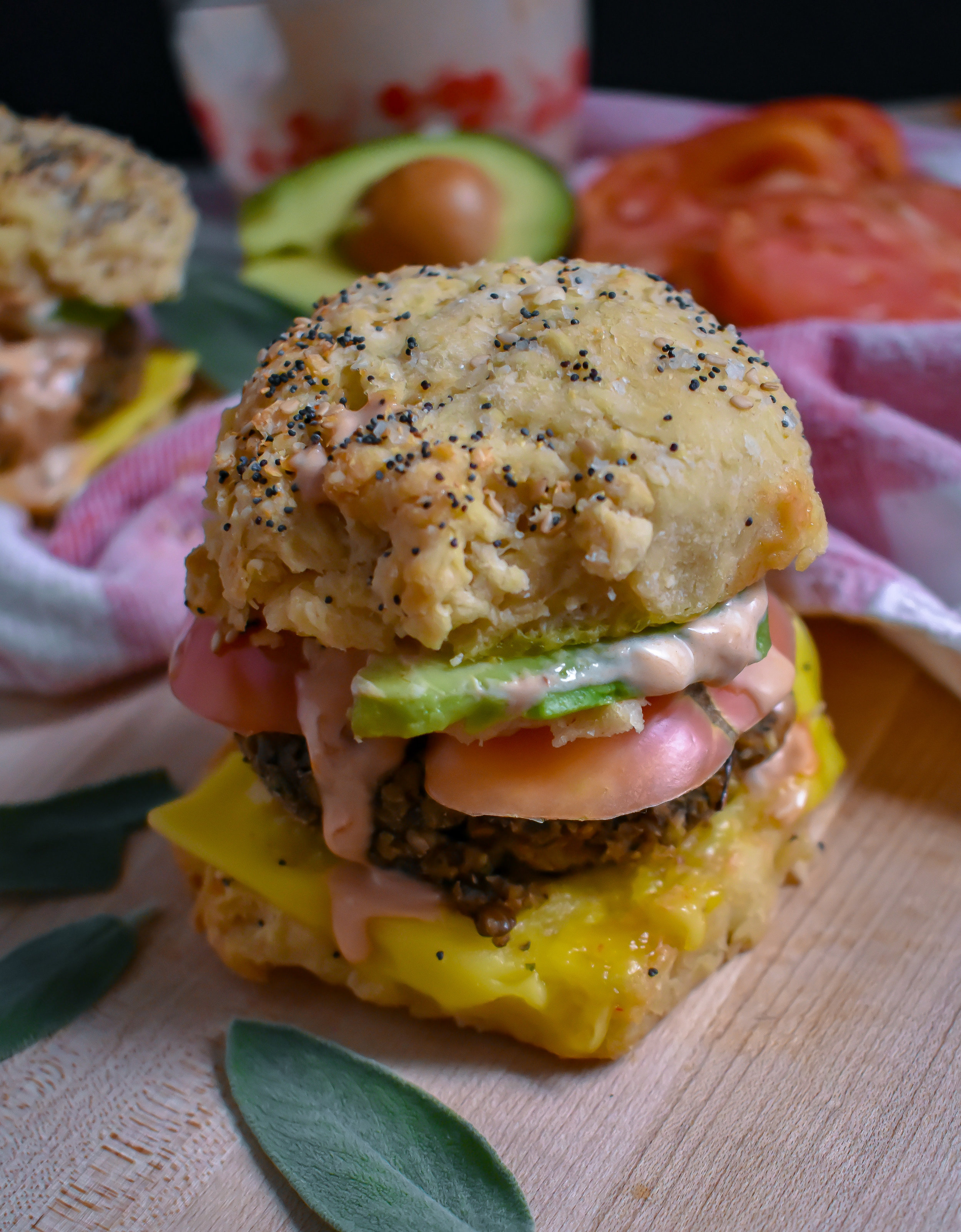 6. Finally, form your biscuit sandwich! Add a layer of vegan cheese to the bottom with a sausage patty, tomato slice, avocado slices, and a healthy layer of chipotle aioli. ENJOY!