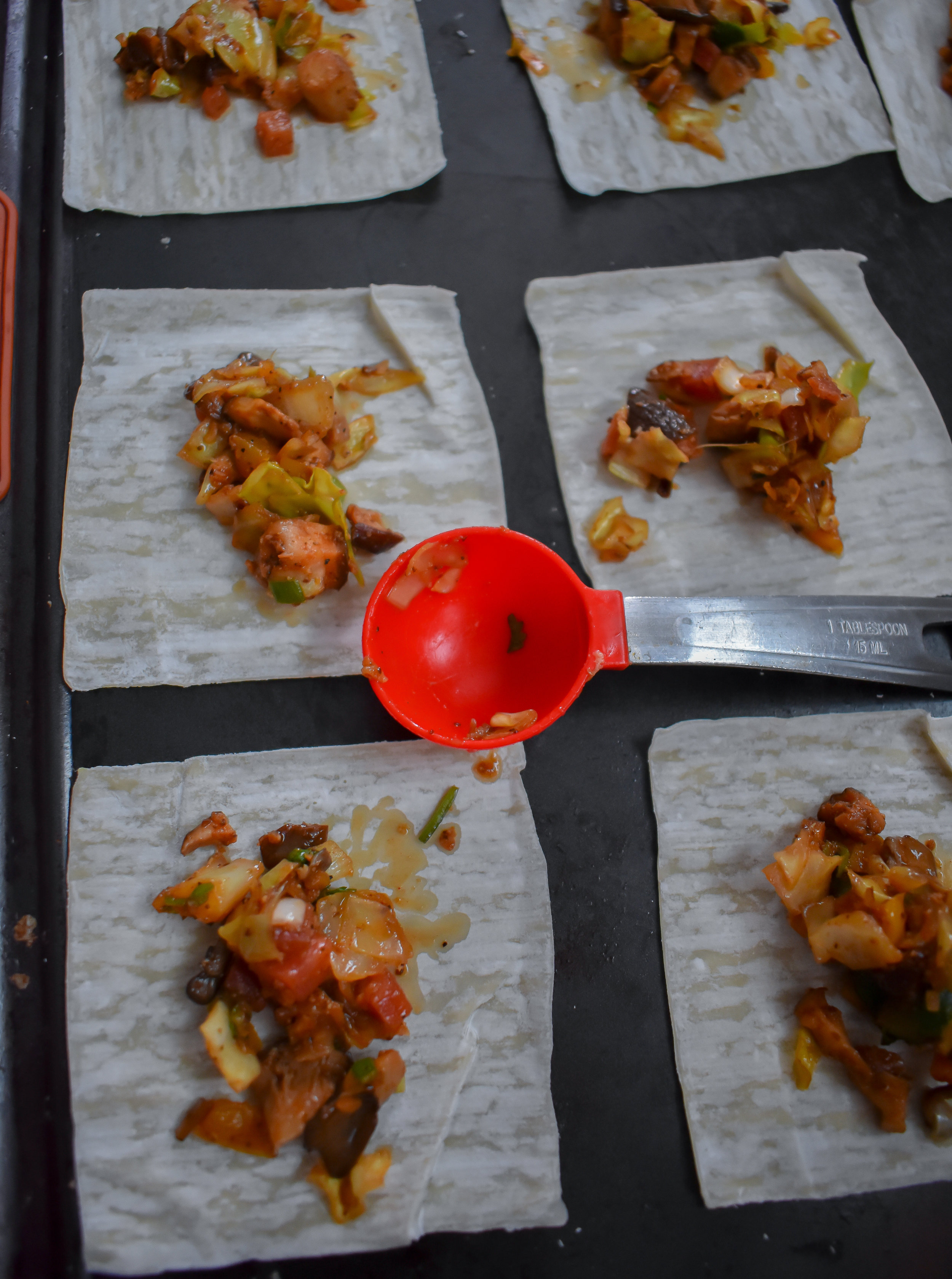 5. To set up your station, line wonton wrappers on a clean baking sheet. Grab a small bowl of water. You'll need a tablespoon as well. Scoop 1 tbl of the filling onto the wrappers. You can do all of them on the sheet at one time. You'll do a couple rounds.