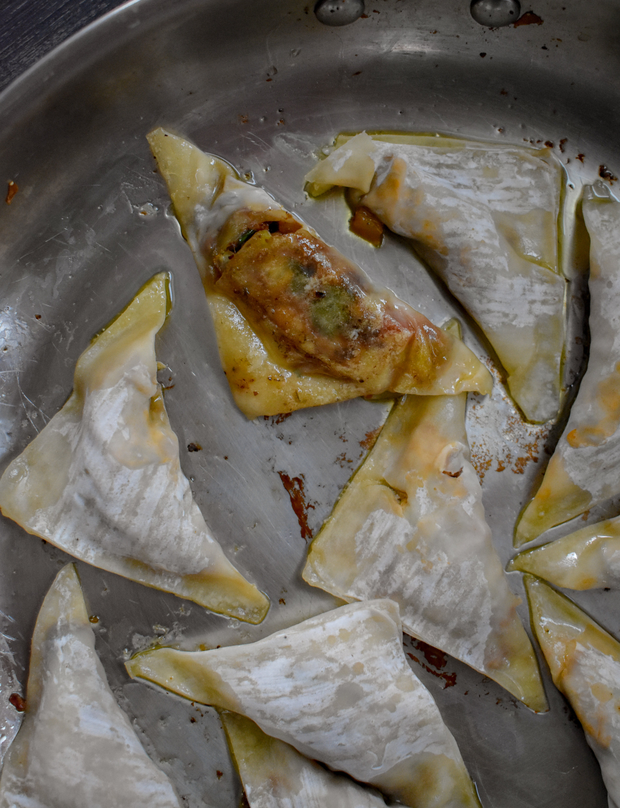 7. To finish the wontons, add to a large frying pan with 2 tsp of sesame oil + 1 tsp of neutral oil. Fry for 4 minutes over medium heat then add 1/4 cup of water and steam for another 4 minutes until the water is evaporated. This process pan fries and steams it.