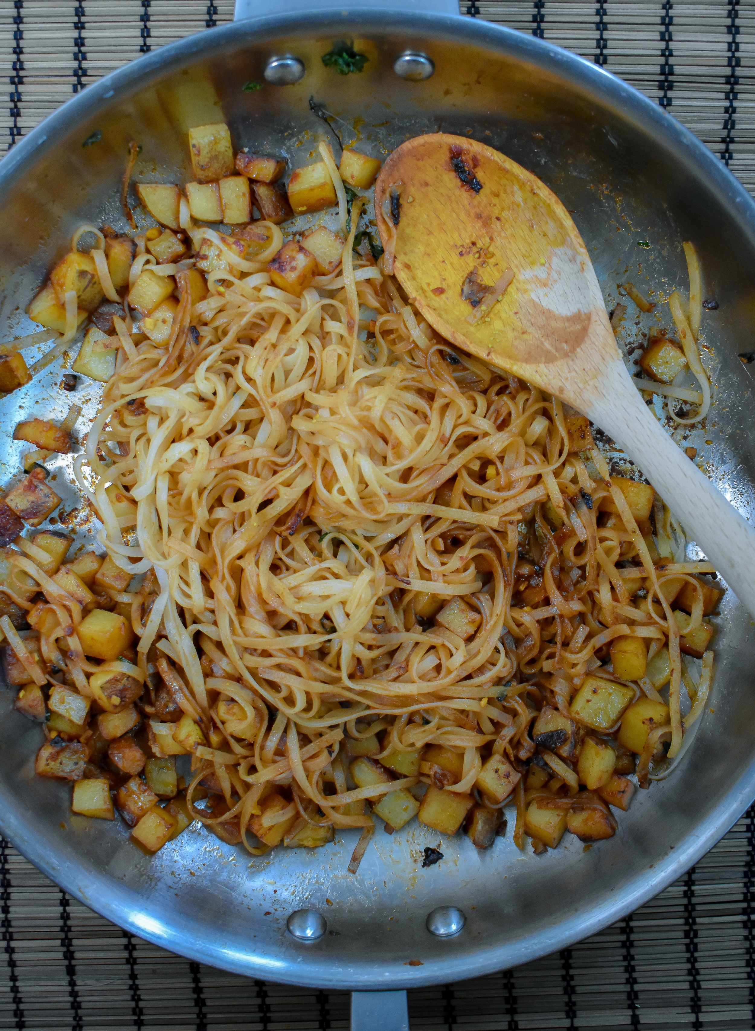 5. After cooking potatoes for about 6 minutes, throw in noodles as well as the pad thai sauce and cook for another 2-3 minutes. Set aside.