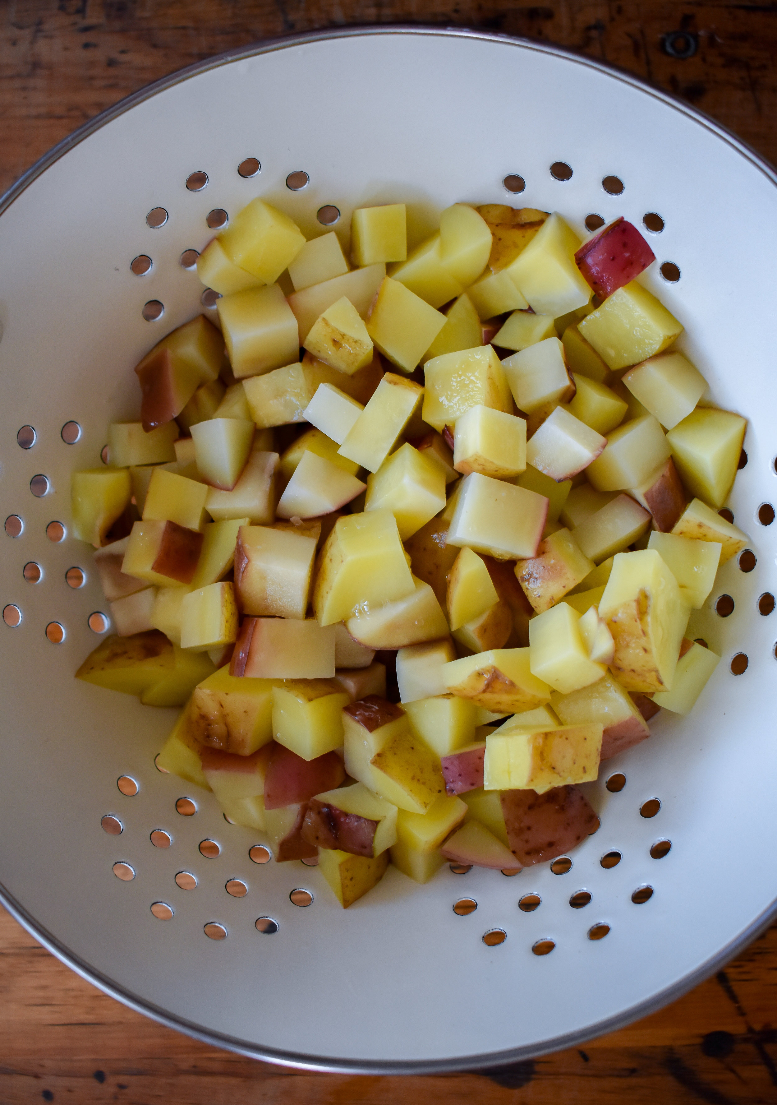 1. To start, add potatoes to a large microwave-safe bowl with 2 tbl of water. Microwave for 7-8 minutes to parboil potatoes.