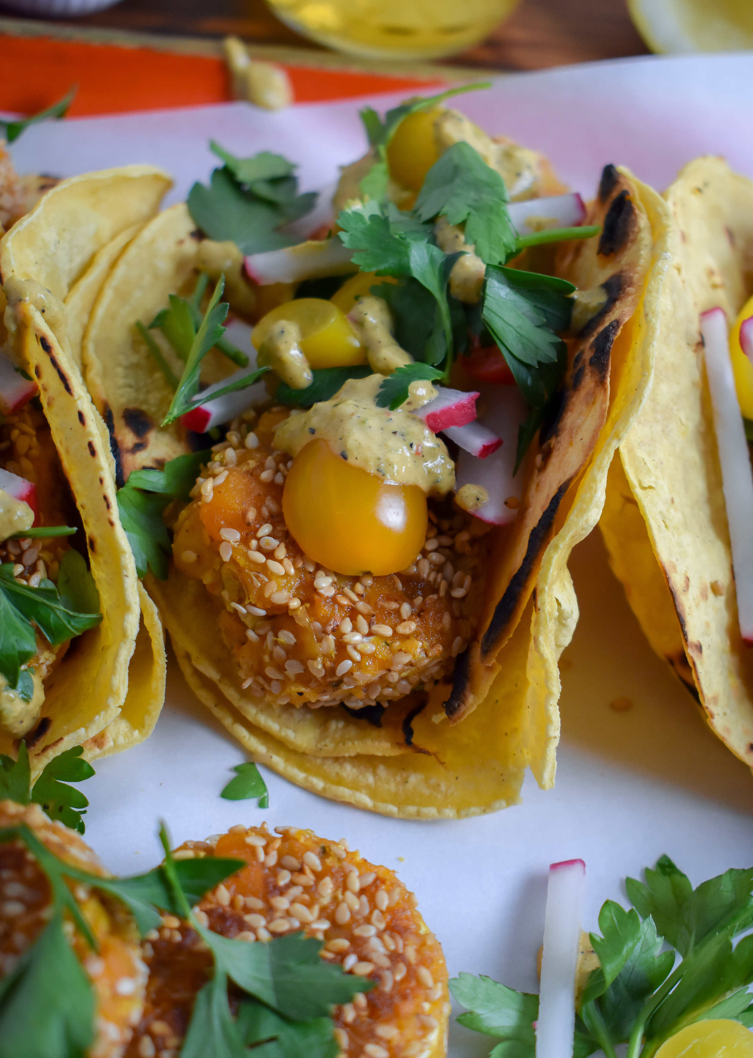 8. To finish, toast up corn tortillas (double up per tacos), then layer on falafel, charred poblano sauce, tomatoes, cilantro/parsley, radishes, and a squeeze of lemon juice.
