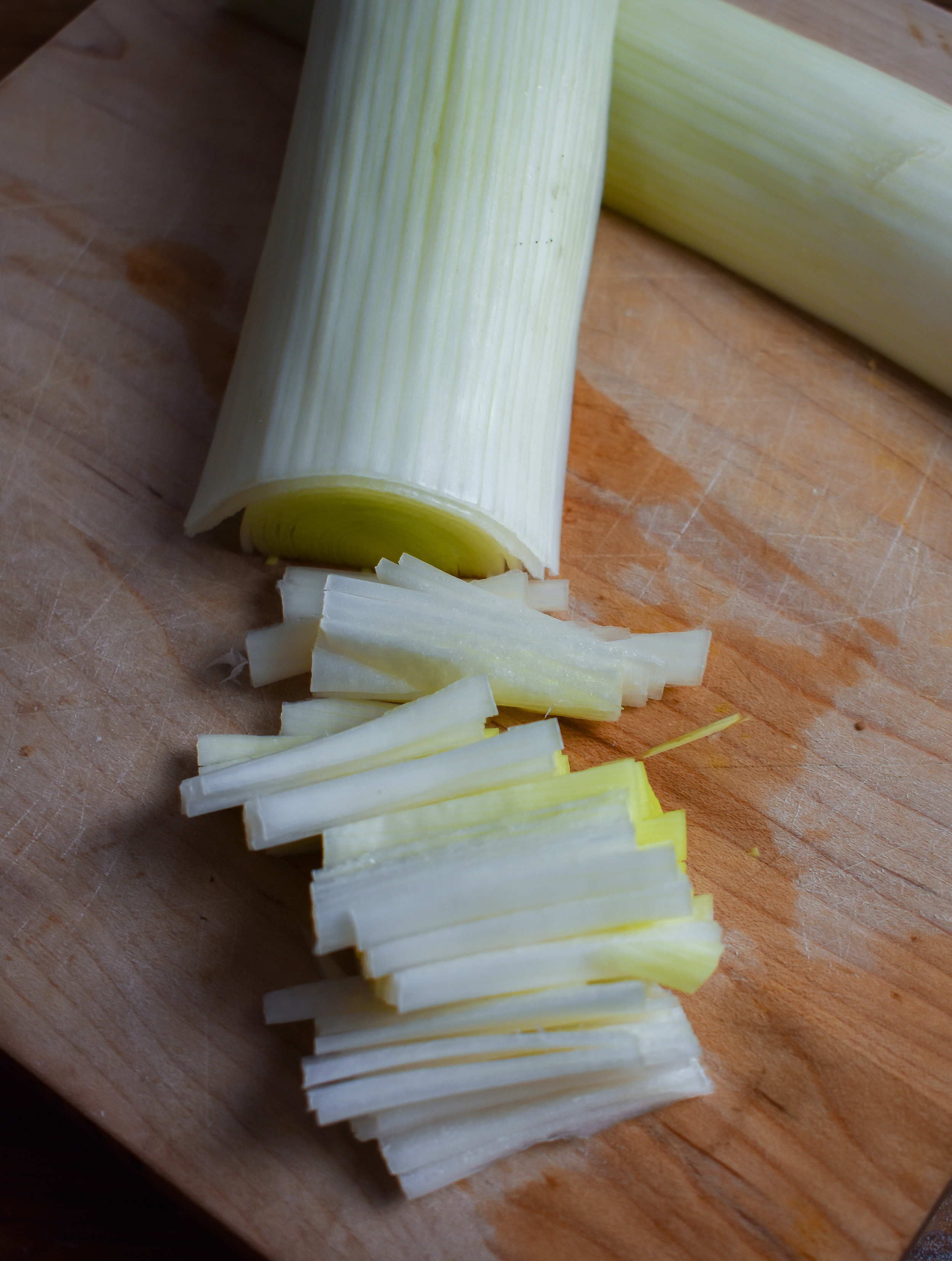 4. For the leeks, place a pan on the stove over medium heat with the oil. To chop the leeks, cut in half, then in 2 inch segments, then cut longwise to make into small matchsticks.