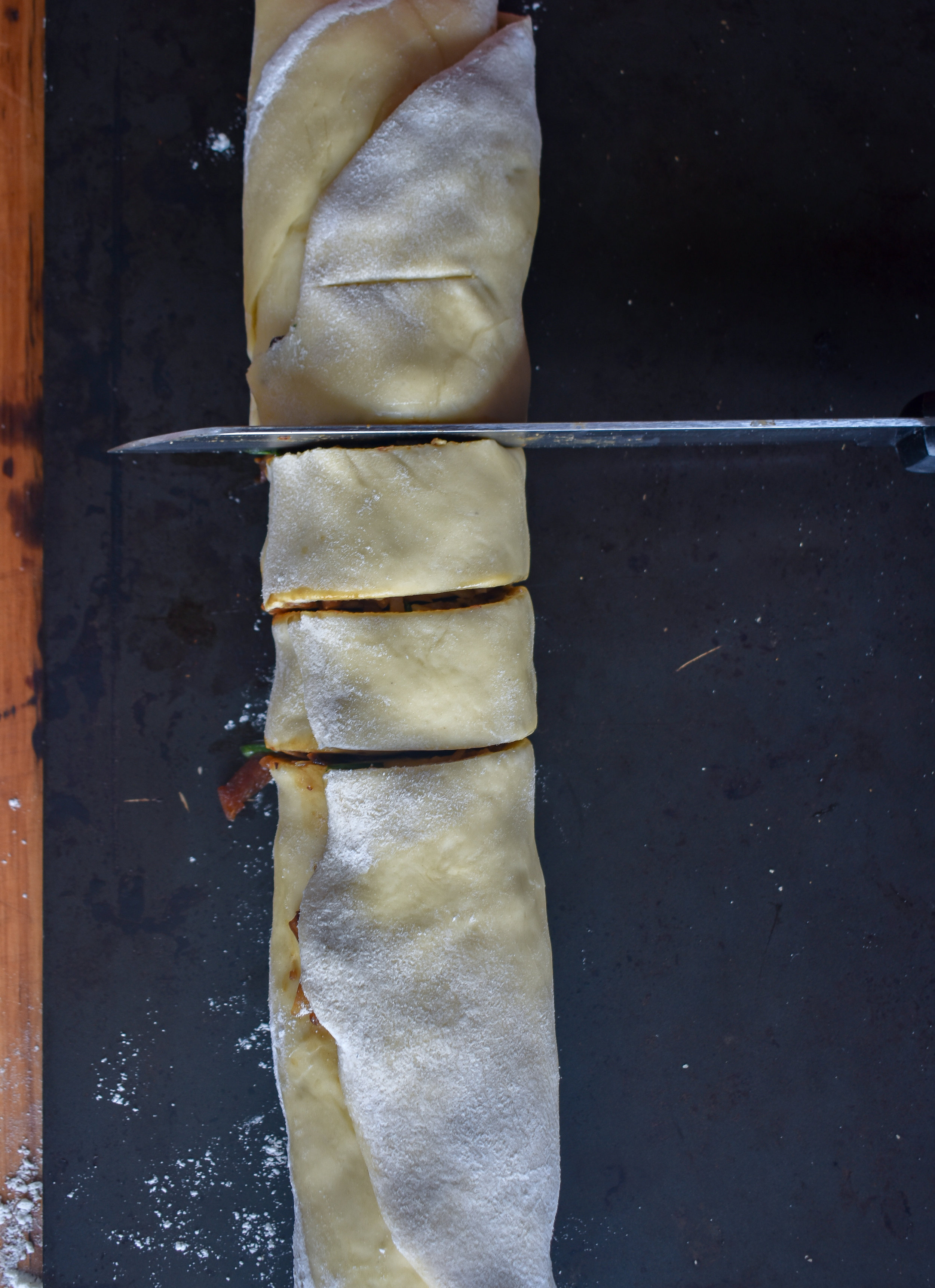 12. After pulling from the freezer, cut into 1-1.5 inch segments. I prefer a bread or serrated knife that saws rather than pushes down. You want the dough's integrity to stay firm. If you are cutting down and the edges are dropping in, you'll want to freeze longer or switch knives.