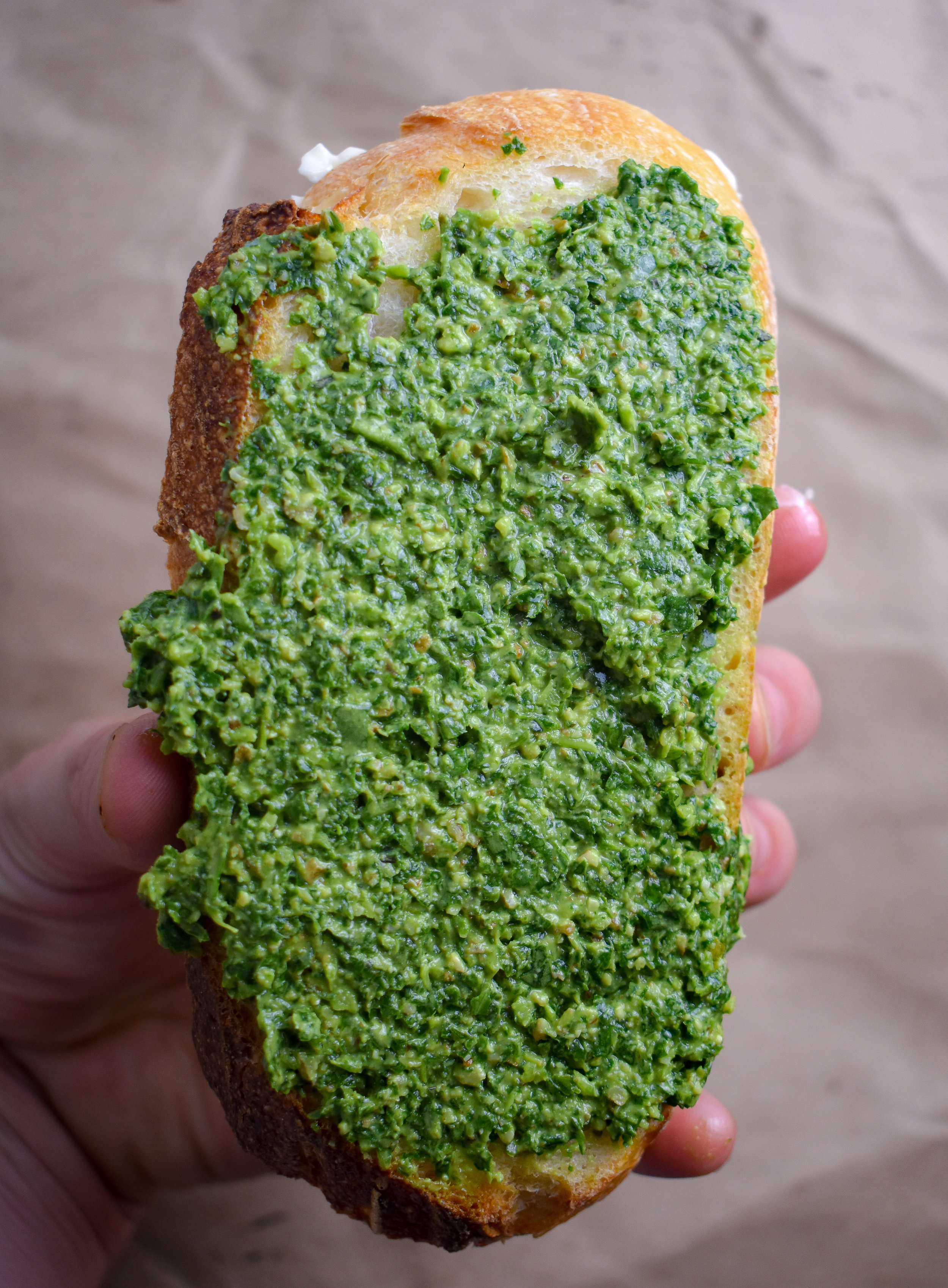 9. With the rest of the bread, butter one side and carefully spread pesto to the other side. Then, place the pesto side onto the cheese mixture side so that the second buttered side is facing up.