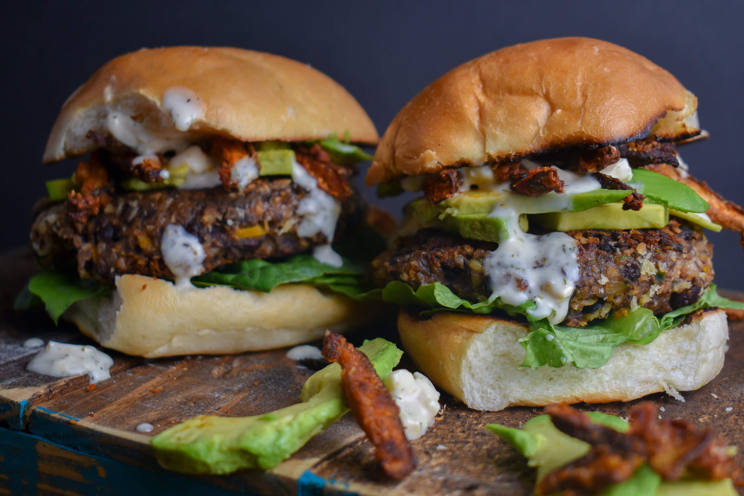 9. To put it all together, serve a toasted bun, with a layer of romaine, then the patty, add avocado slices, pour on the blue cheese sauce, and top with shiitake bacon. Serve!