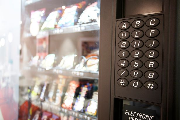 stock-photo-a-man-standing-in-front-of-a-vending-machine-414731824.jpg