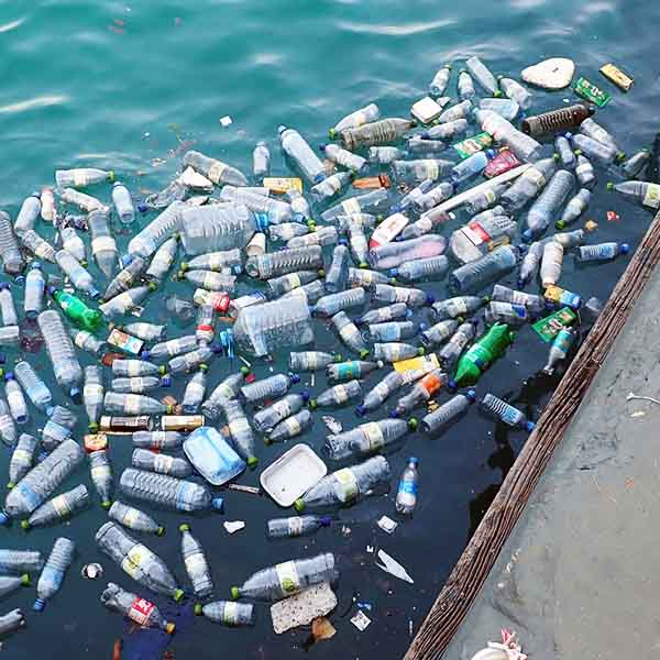 Large amounts of wasted plastic bottles and packaging floating in ocean.