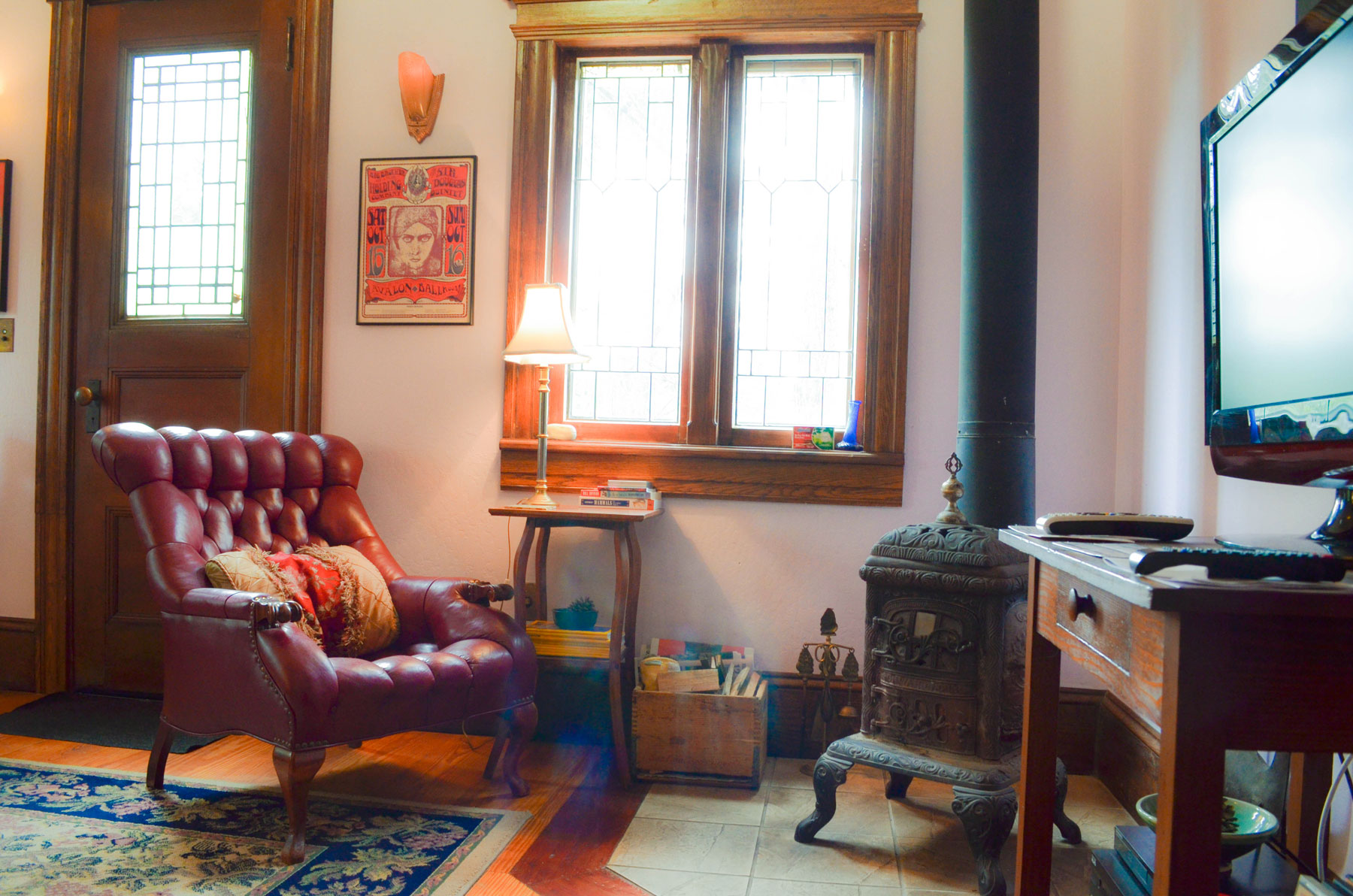 a comfy leather chair by a wood burning stove in the Bridge Cottage at B. Bryan Preserve
