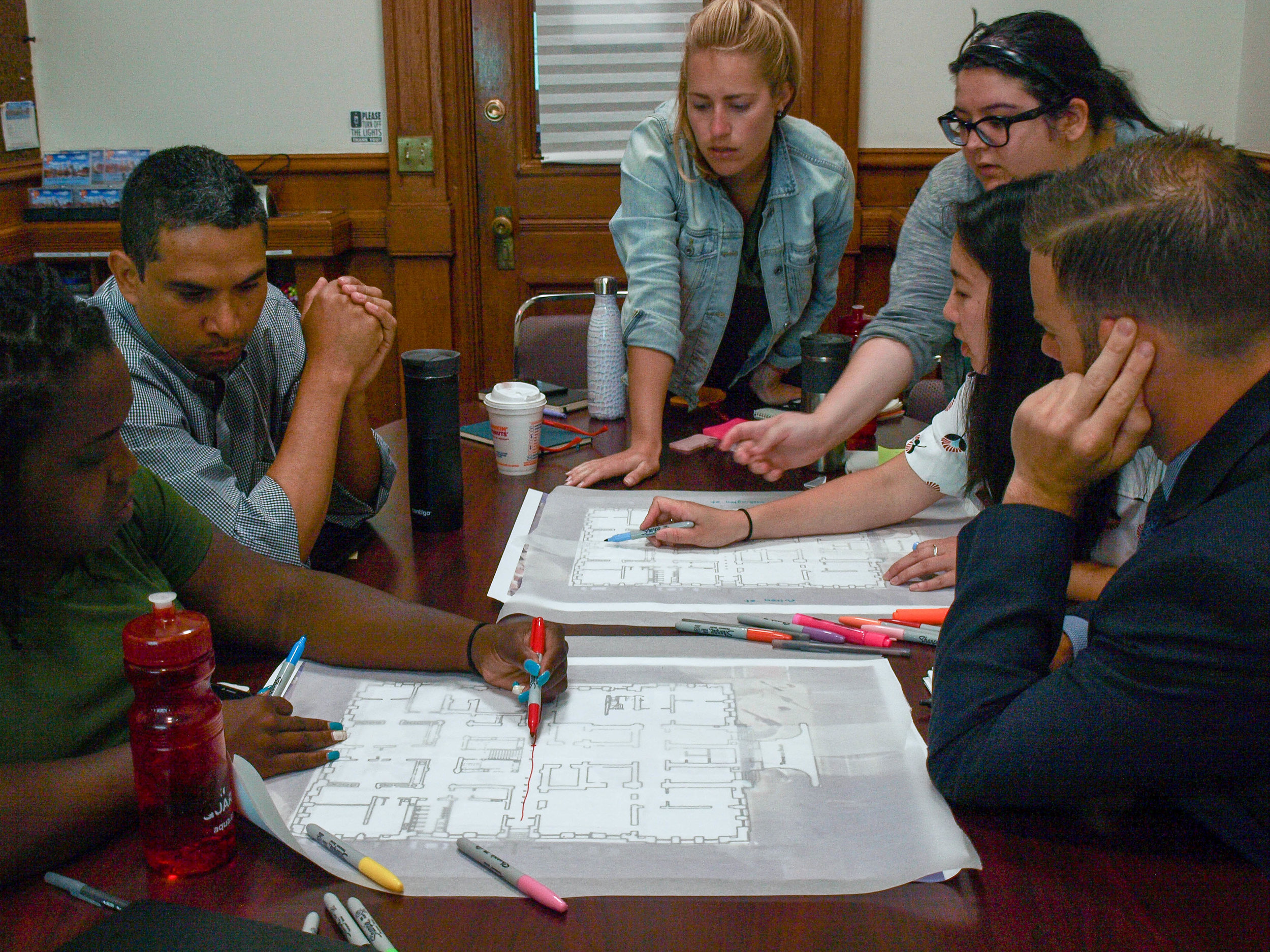 two groups working through the entry sequence of city hall during the design thinking workshop