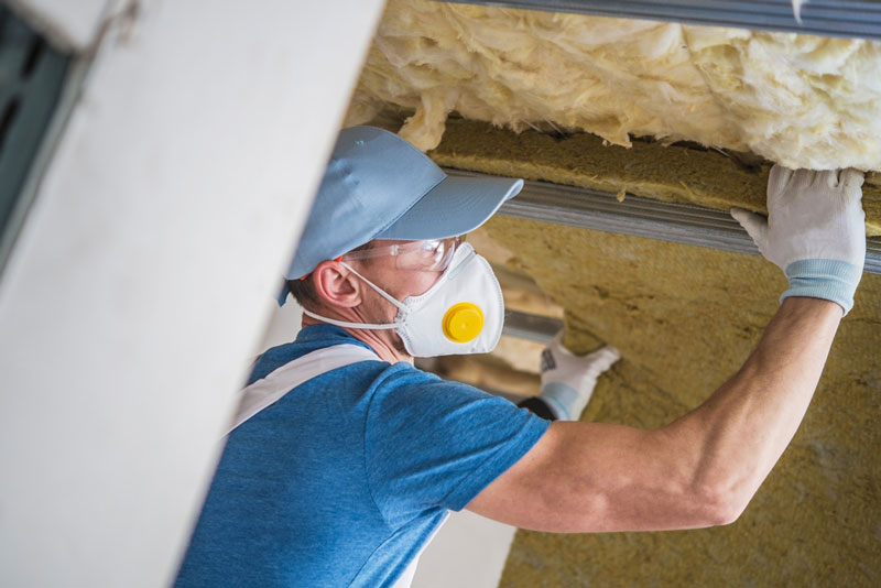 man-adding-insulation-above-him-in-garage