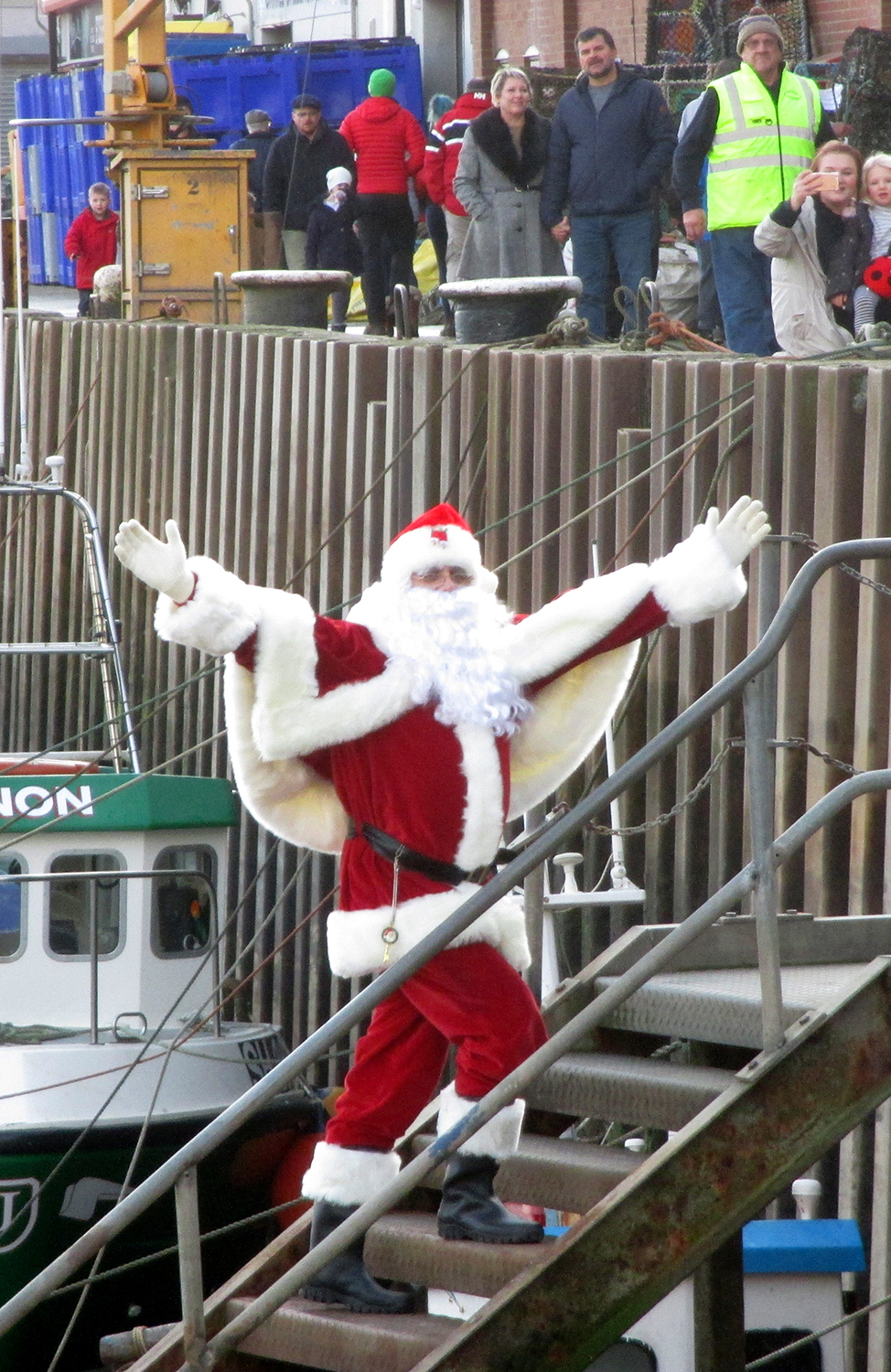 Santa climbs the steps from the boat to the pier