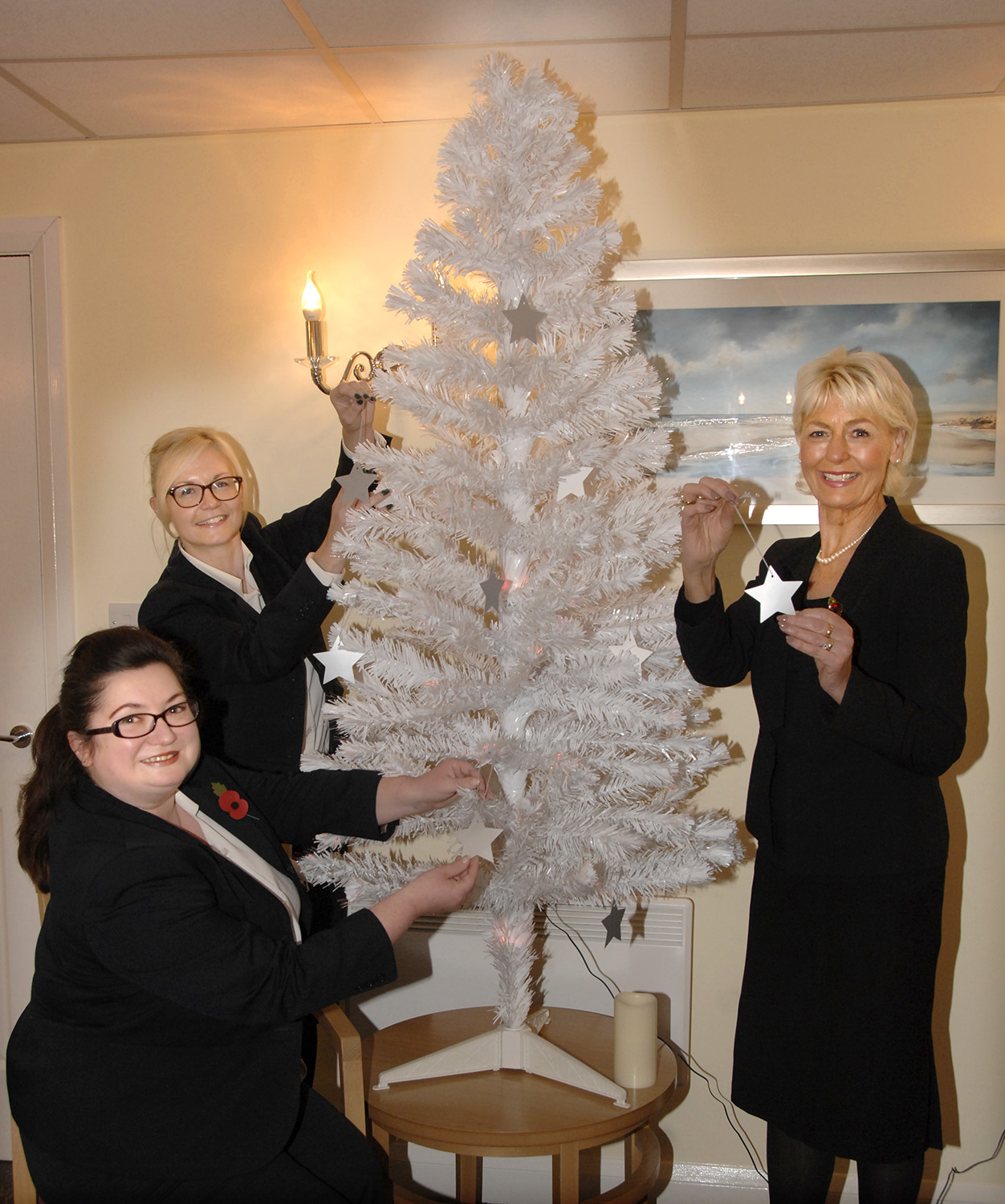 L-R, Rachael Green, Emma Kneeshaw and Ann Kitto place Christmas stars on a Christmas tree (to order photos ring 353597)