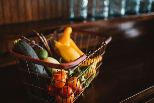Wire basket full of fresh vegetables on wooden table