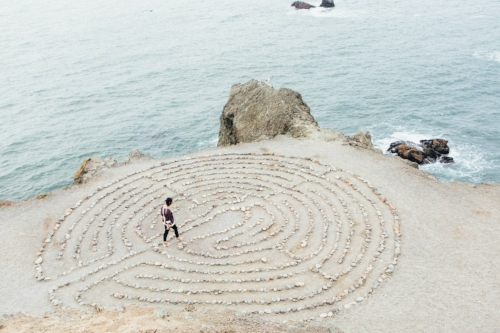 Zen rock meditation circle with woman walking through on seashore
