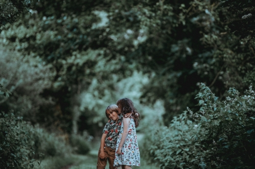 Two young kids kiss in a forest