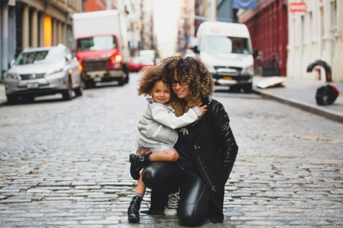 Young African American mother with her daughter in the street in New York
