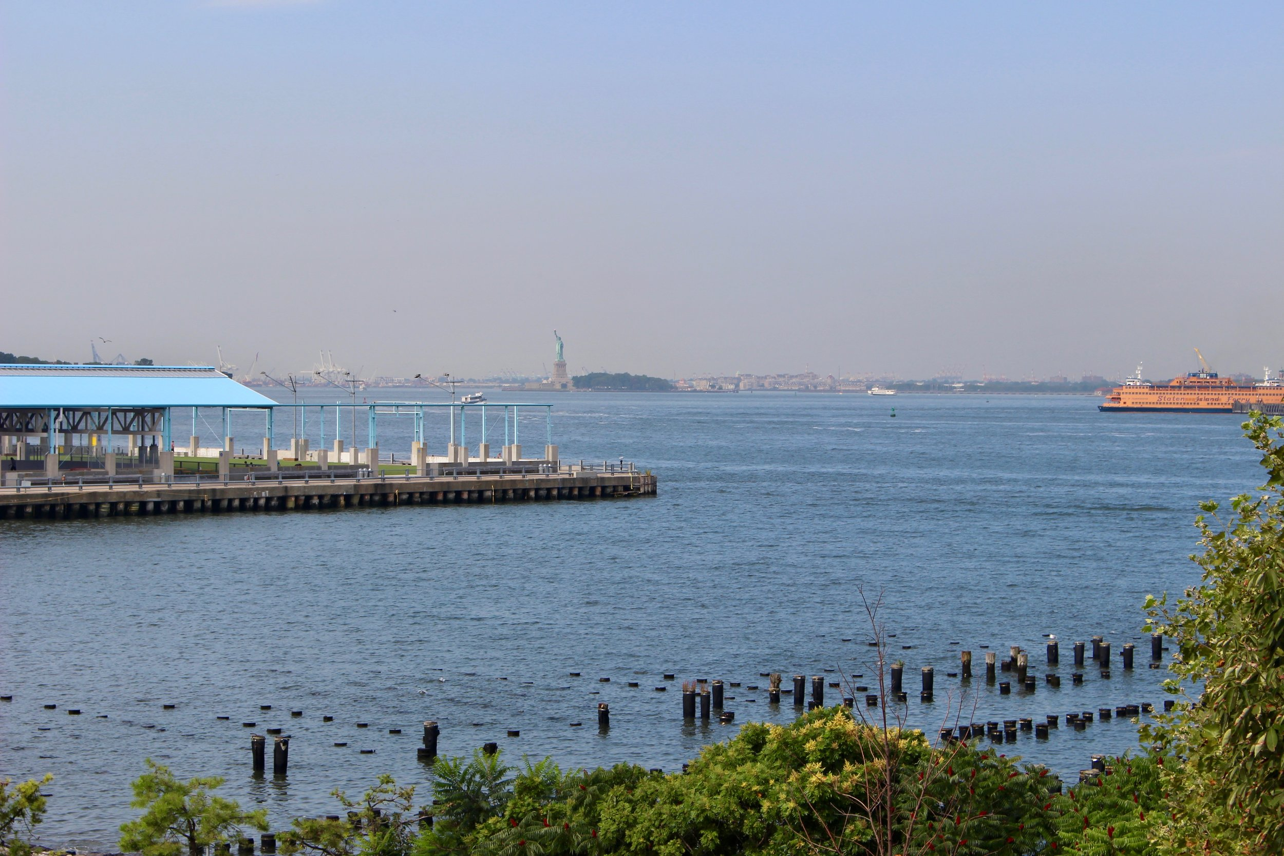 """Reaching the end of the footbridge and stepping out onto the path, here is the view. Note the Staten Island Ferry making its way into the Harbor and the Statue of Liberty.It is always breath taking, no matter how many times you approach this """"vista."""""""