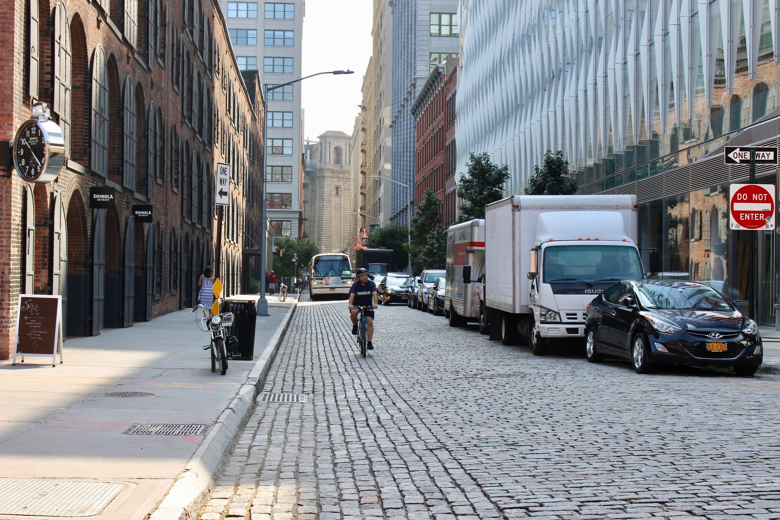 Looking north on Water Street. Past Main Street you can see the Manhattan Bridge stanchion. Note the cobble stone street, which is the case throughout DUMBO. Bicyclists, buses, cars, and pedestrians happily go about their business on the narrow DUMBO streets.