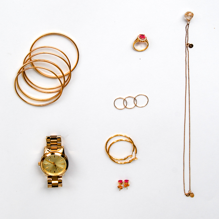 - Jewelry - set of gold bangles, gold ring with ruby stone, skinny gold necklace, stack of skinny rings, gold hoops, studs, watch