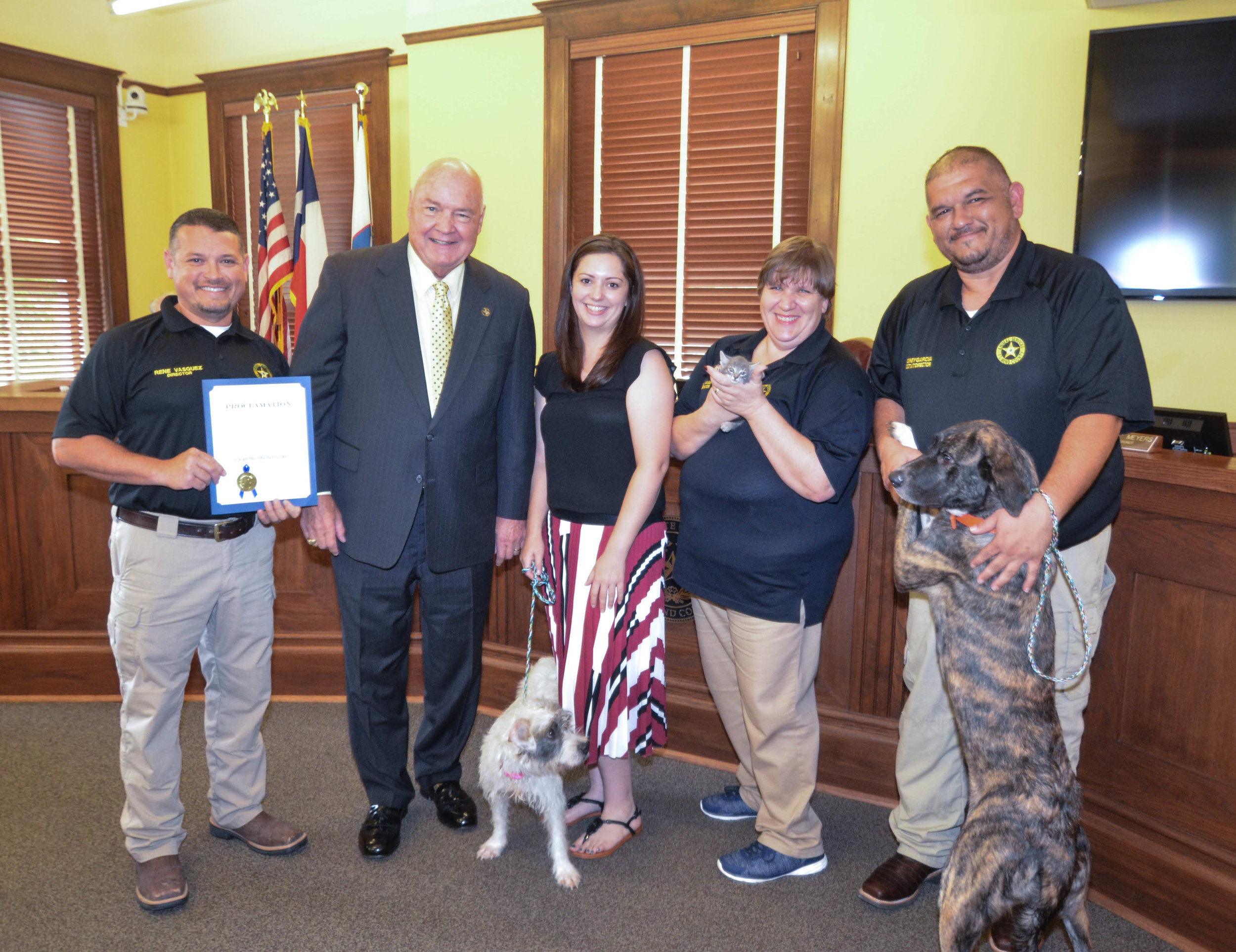 Pictured from Left to Right: Rene Vasquez, Fort Bend Animal Services Director; Fort Bend County Judge Bob Hebert; Dr. Andrea Muegge, Fort Bend Animal Services Veterinarian; Anna the Pup, In Search of Good Home; Barbara Vass, Fort Bend Animal Services Adoption Coordinator; Smokey the Kitty, In Search of Good Home; Rodney Garcia, Fort Bend Animal Services Assistant Director; Tigger the Pup, In Search of Good Home.