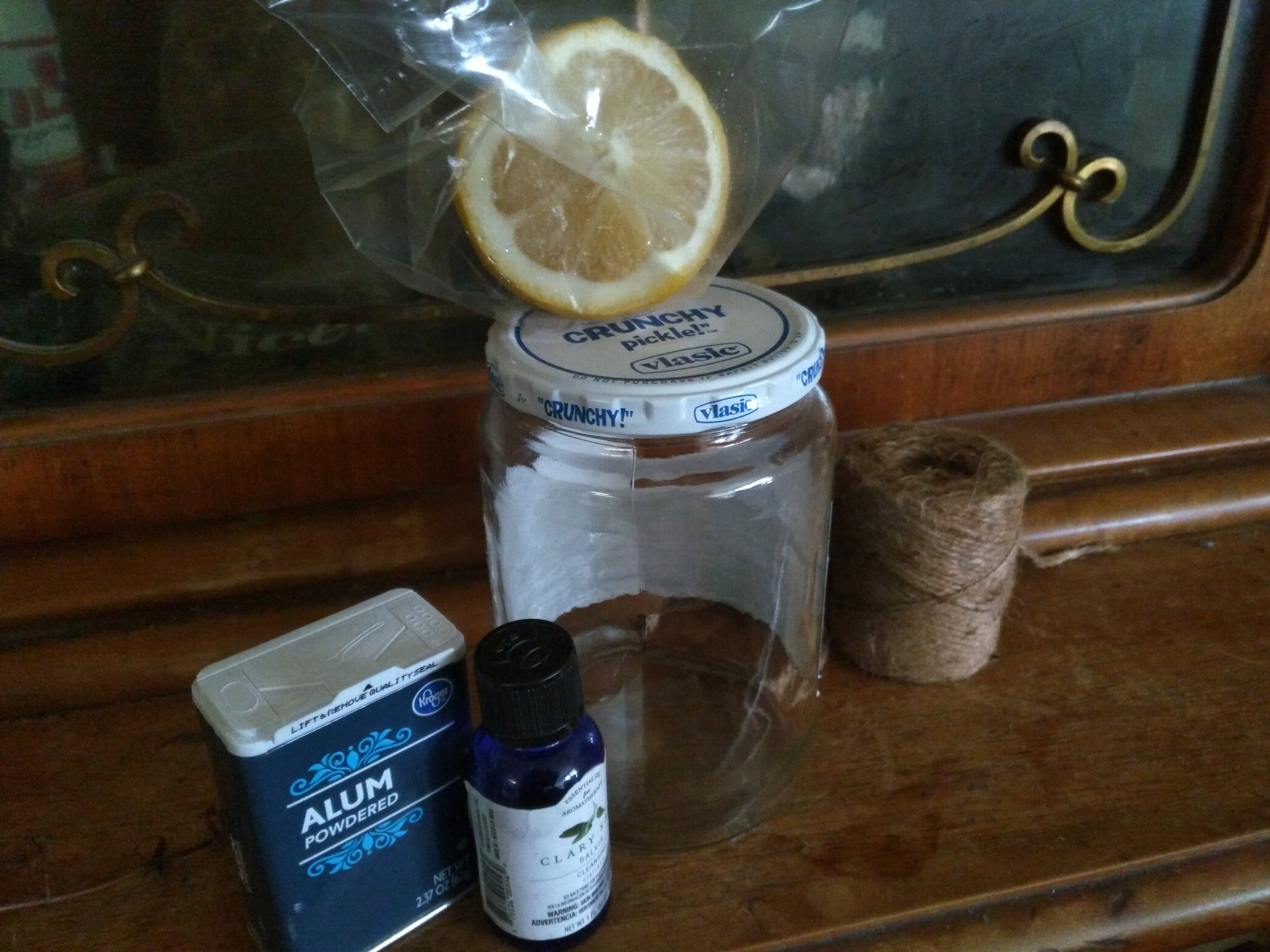 Powdered alum to ward off negative energies, my favorite store-bought fragrance oil (Clary Sage), half a sliced lemon, a Mason jar to hold the wash, and twine to decorate the jar. :)