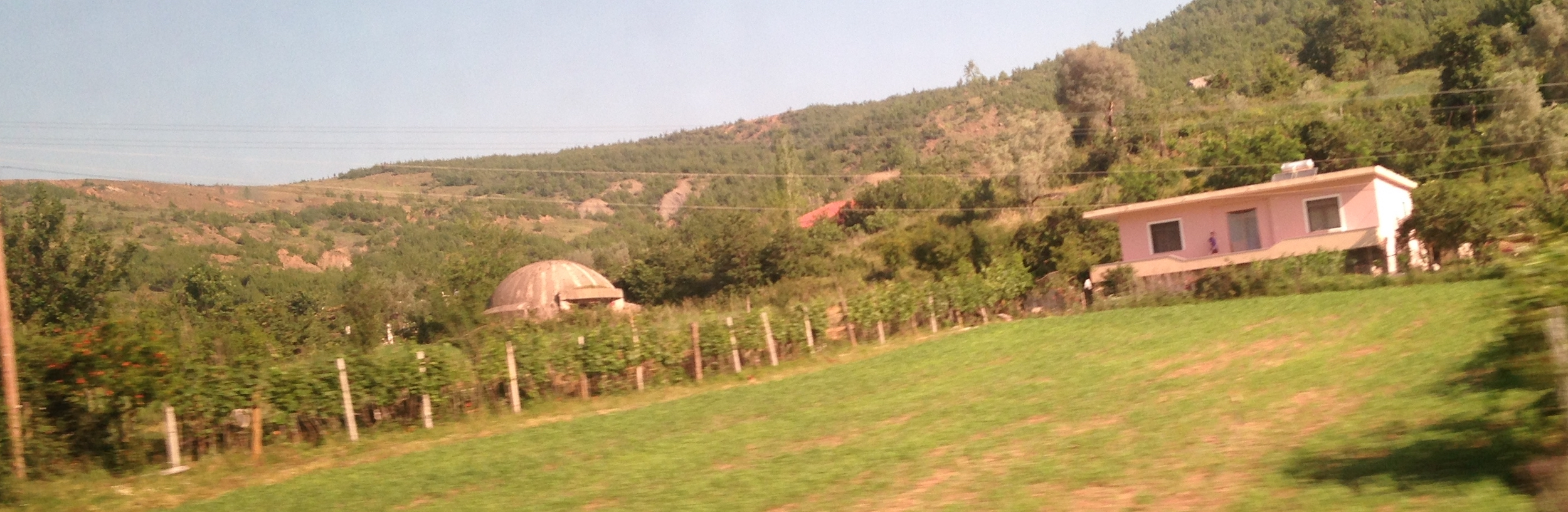Semi circular bunker (left) in farmyard. Photo taken from the mini bus on the road to Tirana.