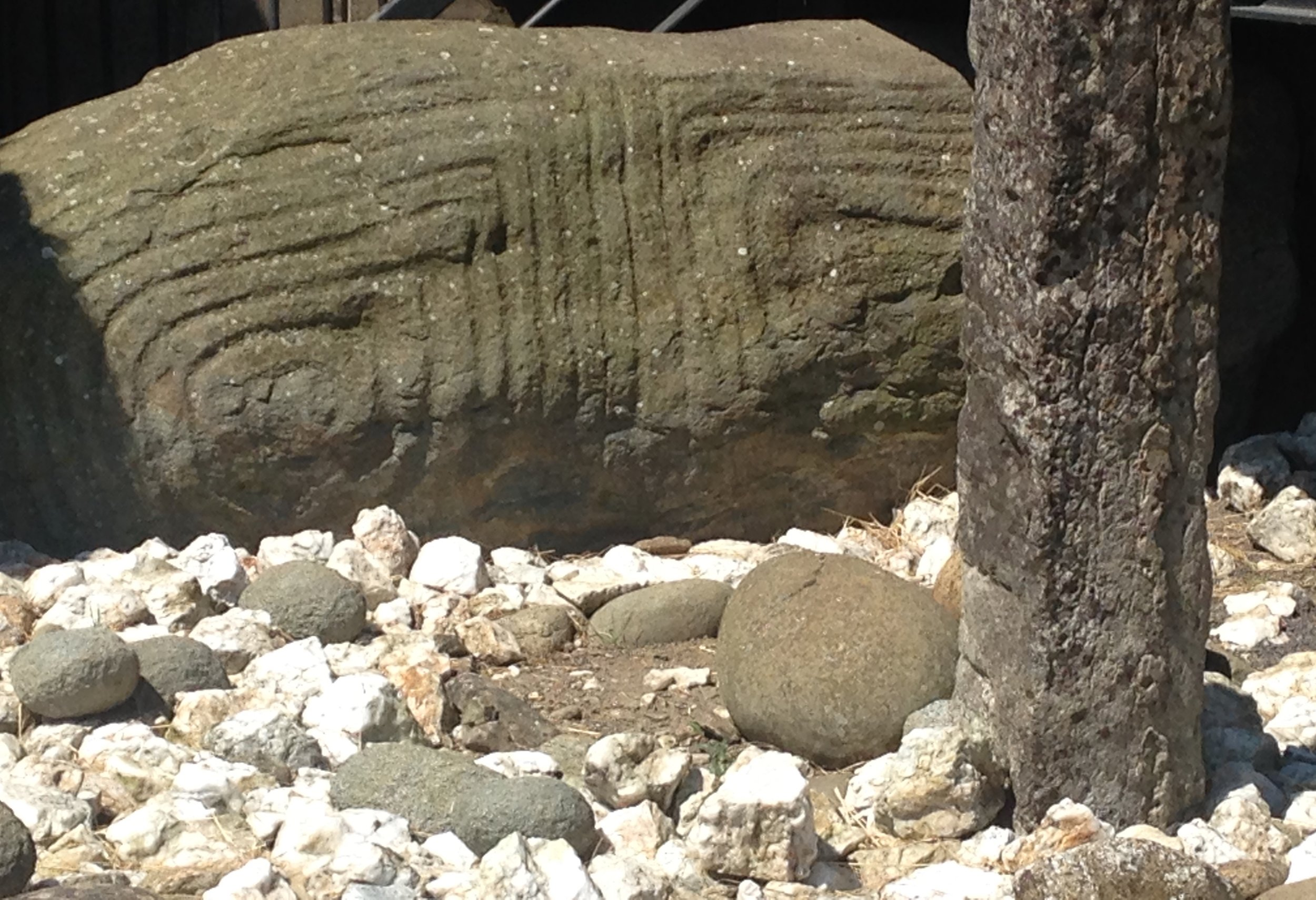 Grooved inscriptions on the entrance rock at Knowth, Ireland showing quartz and round granite rubble at its base.
