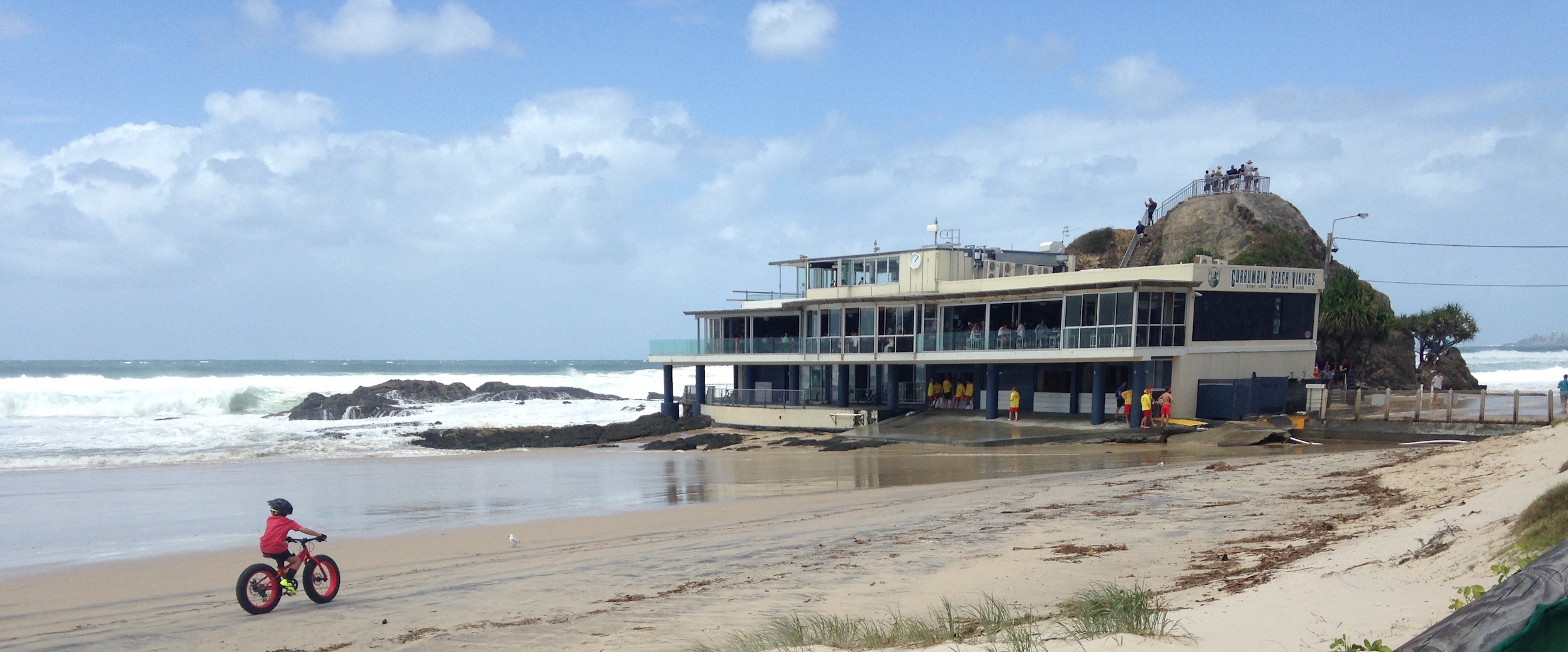 Riding into the wind as Currumbin Beach Vikings Surf Lifesavers gather at their clubhouse amid wild waves.