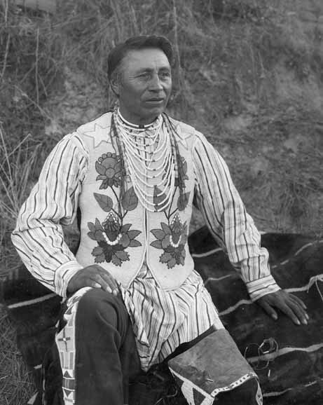 Photograph of man wearing traditional Salish dress by unknown photographer.