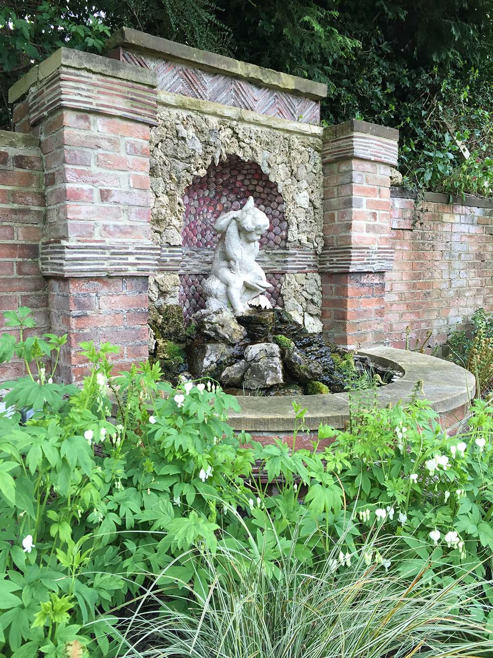 Grotto. Queen scallop shell work by Olicana Mosaics. Plants for shade/ and foliage: Ferns in variety, Dicentra alba, Brunnera Jack Frost.