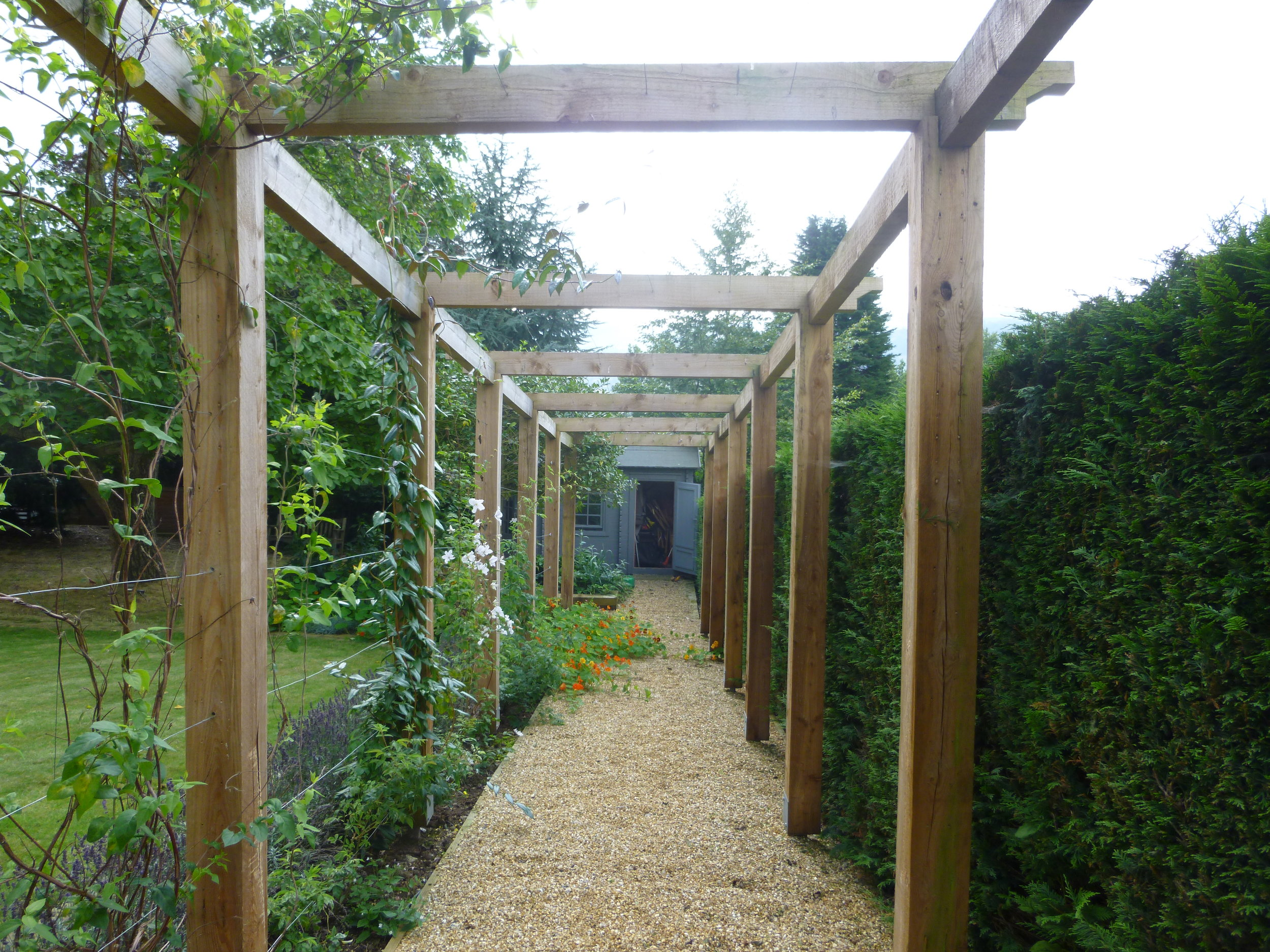 A simple timber pergola defines the gravel path to the vegetable garden.