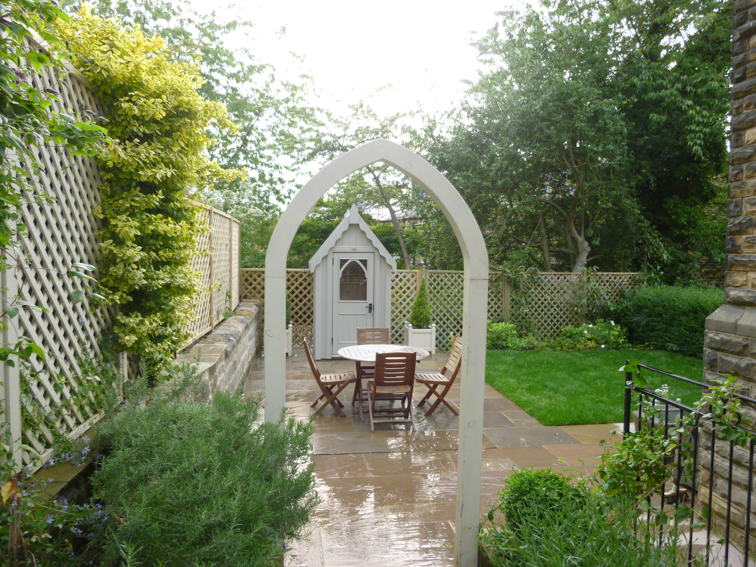 Shed framed by a bespoke 'Gothic' painted timber arch.