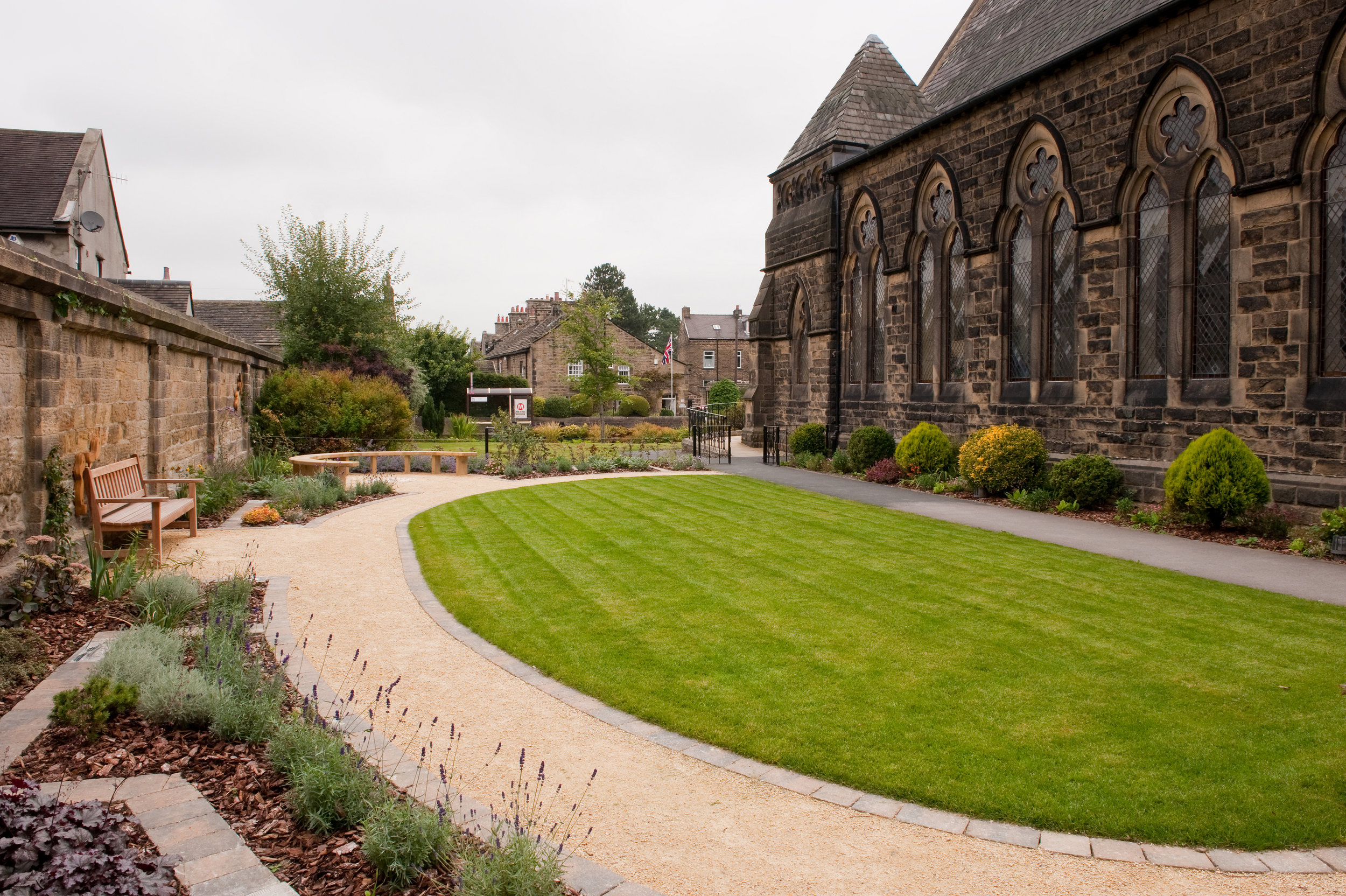 The main garden path in self-binding gravel forms a curve around the new lawn used for summer picnics and games.