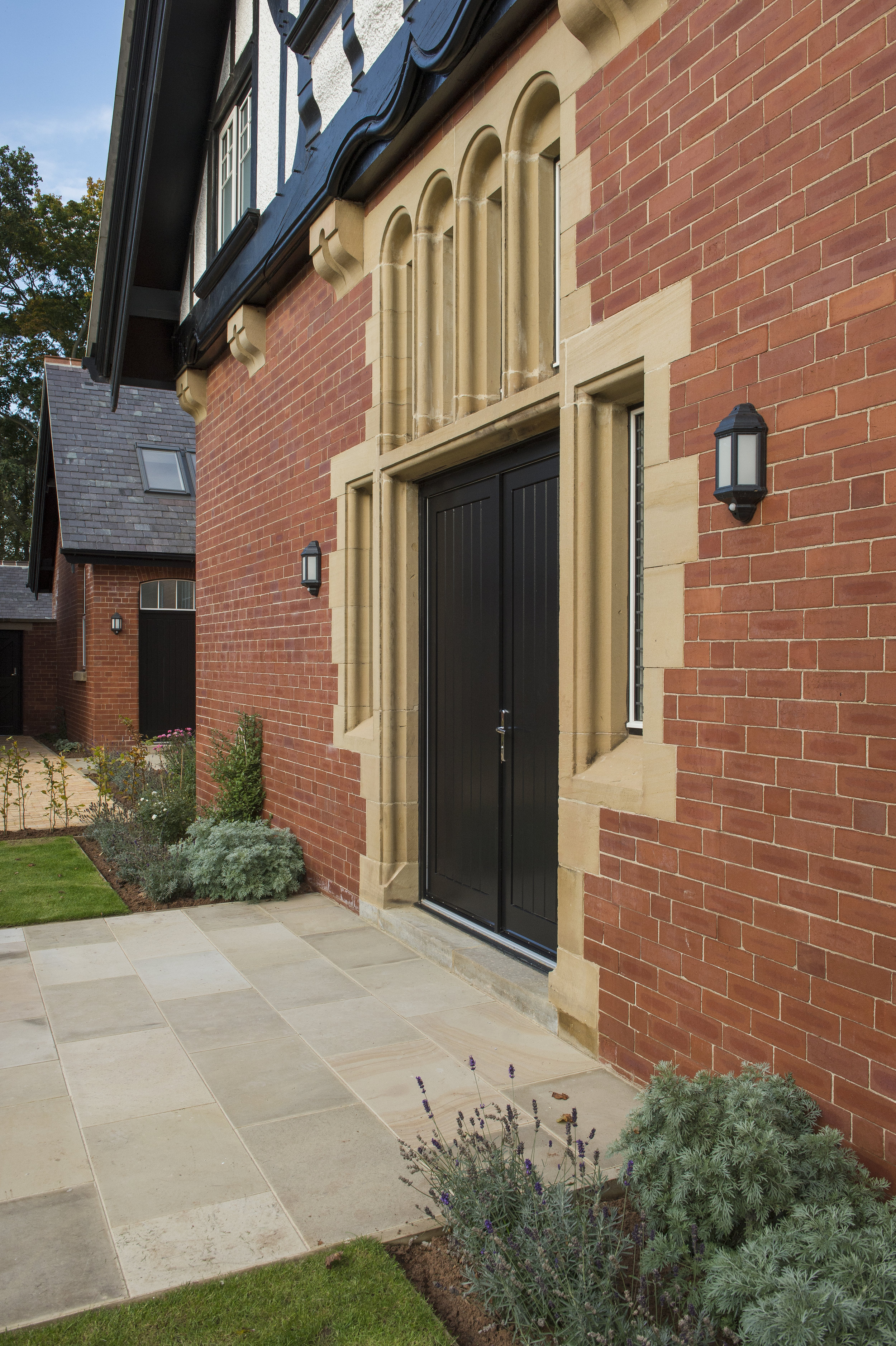 A broad flag path to the main entrance door, framed with ornamental planting and climbers. Path of bricks, reclaimed from the stable building. A beech hedge defines the parking courtyard.