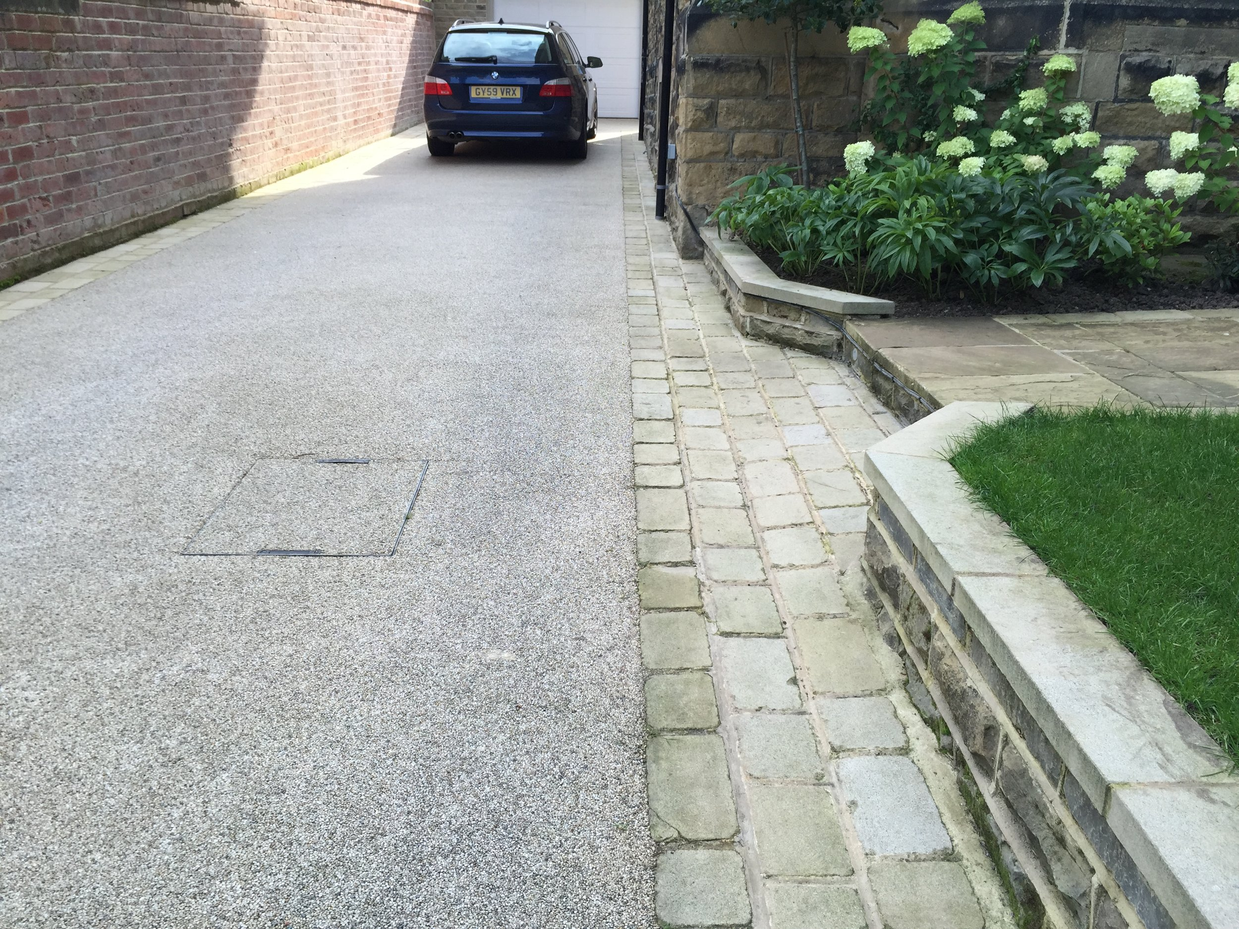 Resin bound drive surfacing with stone sett edging.