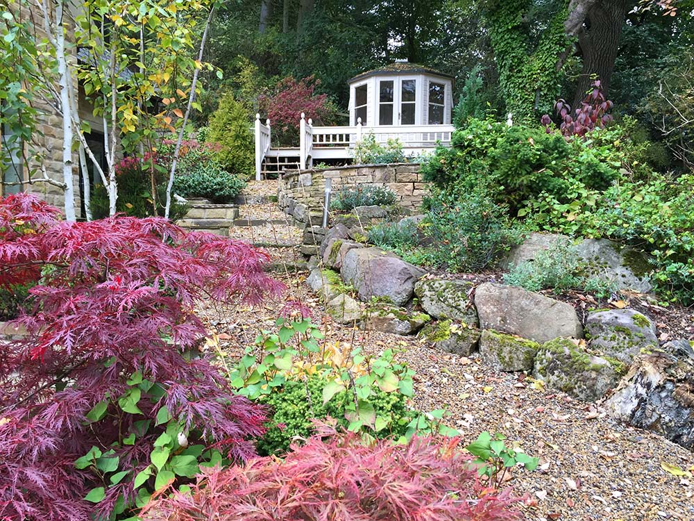 The elevated summer house surveys the woodland garden.