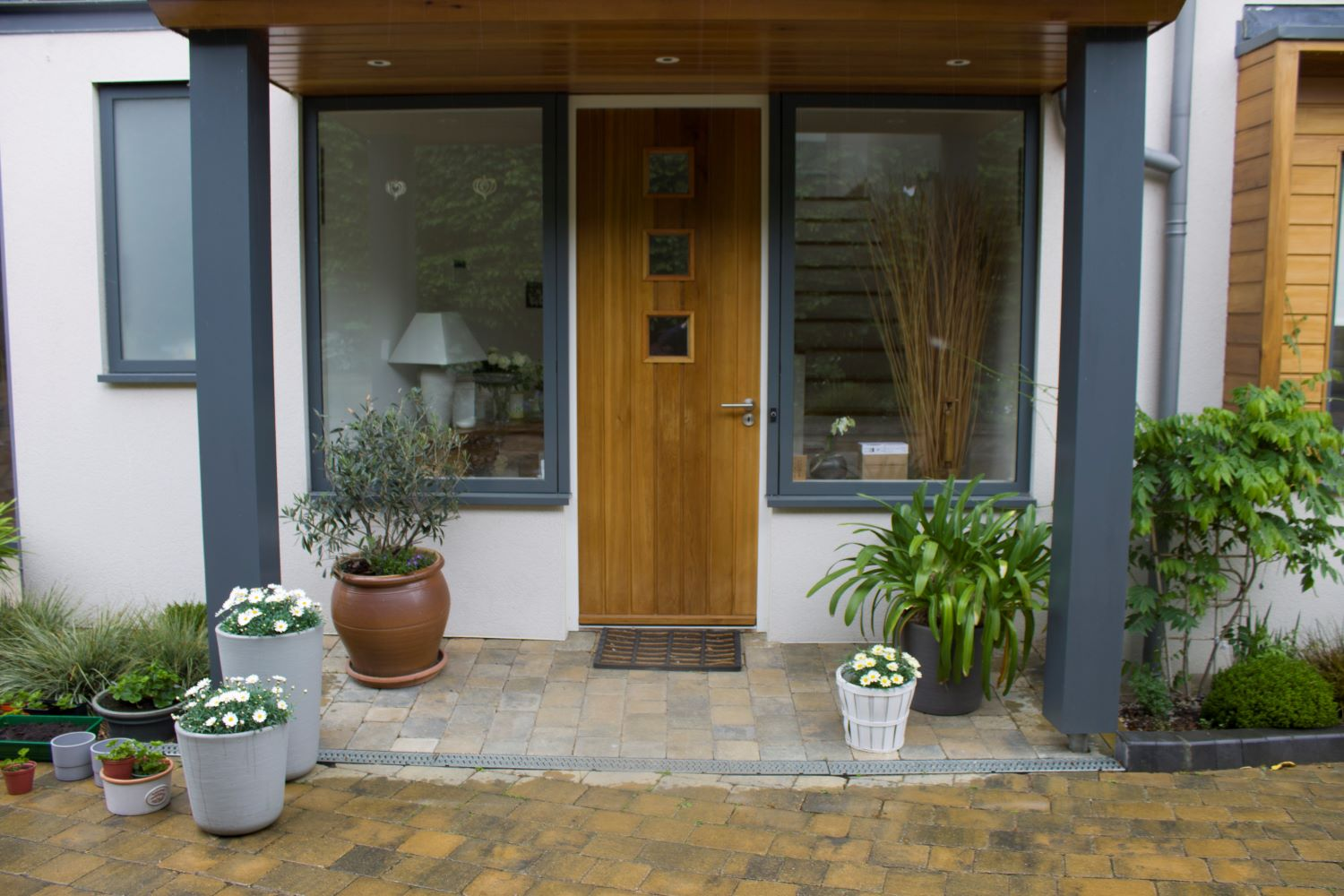 The front door framed by potted plants