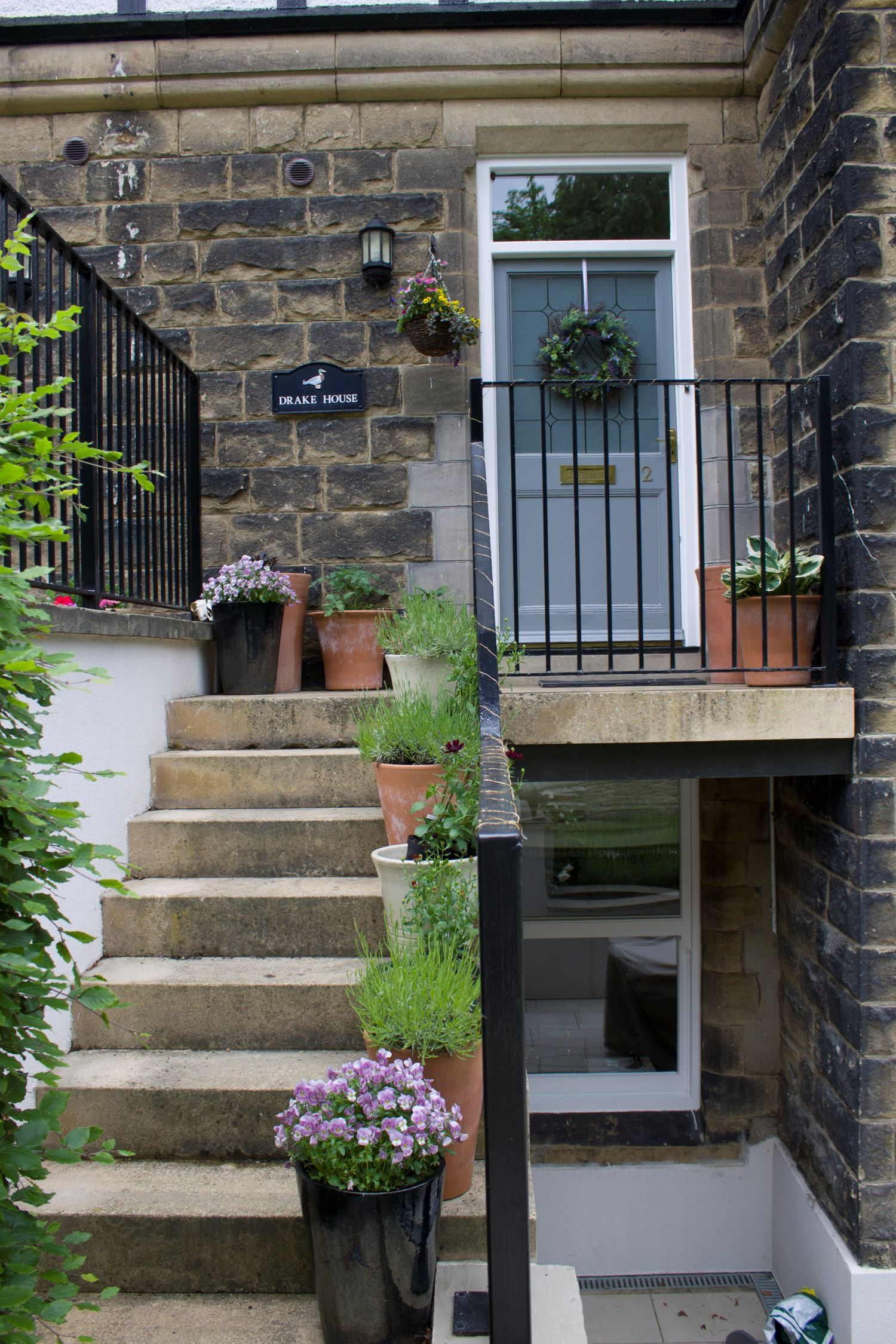 Pretty approach to the front door. The stone steps are softened by potted plants
