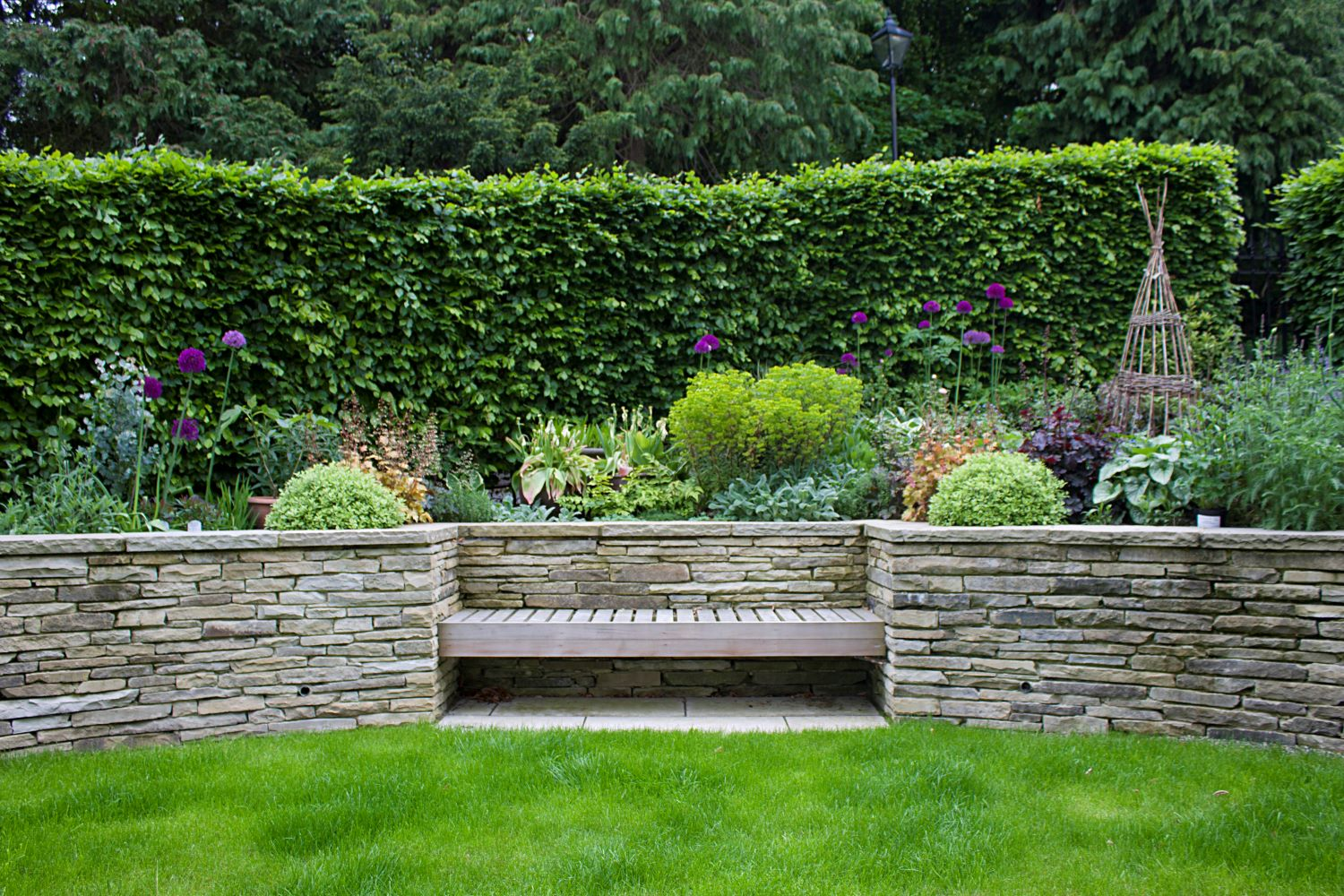 The built-in timber bench in the dry stone wall