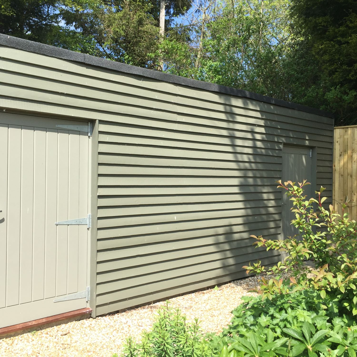 The former garage, disguised with painted timber cladding, makes a smart garden store